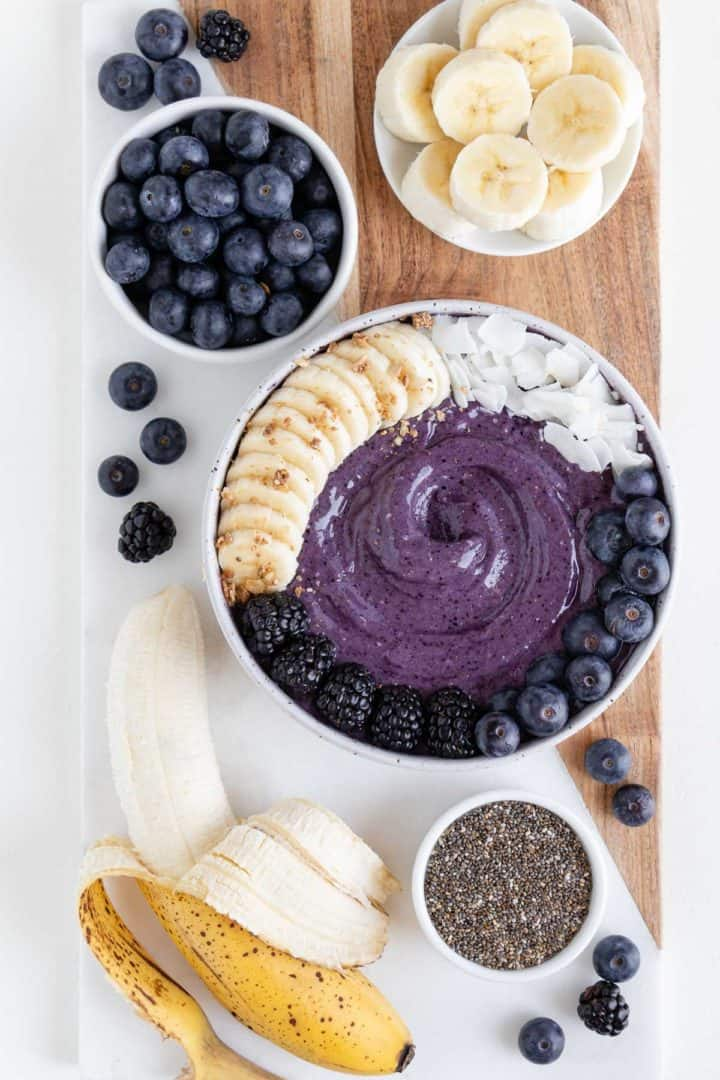a wood and marble cutting board topped with a blueberry banana smoothie bowl, ripe banana, chia seeds, and berries