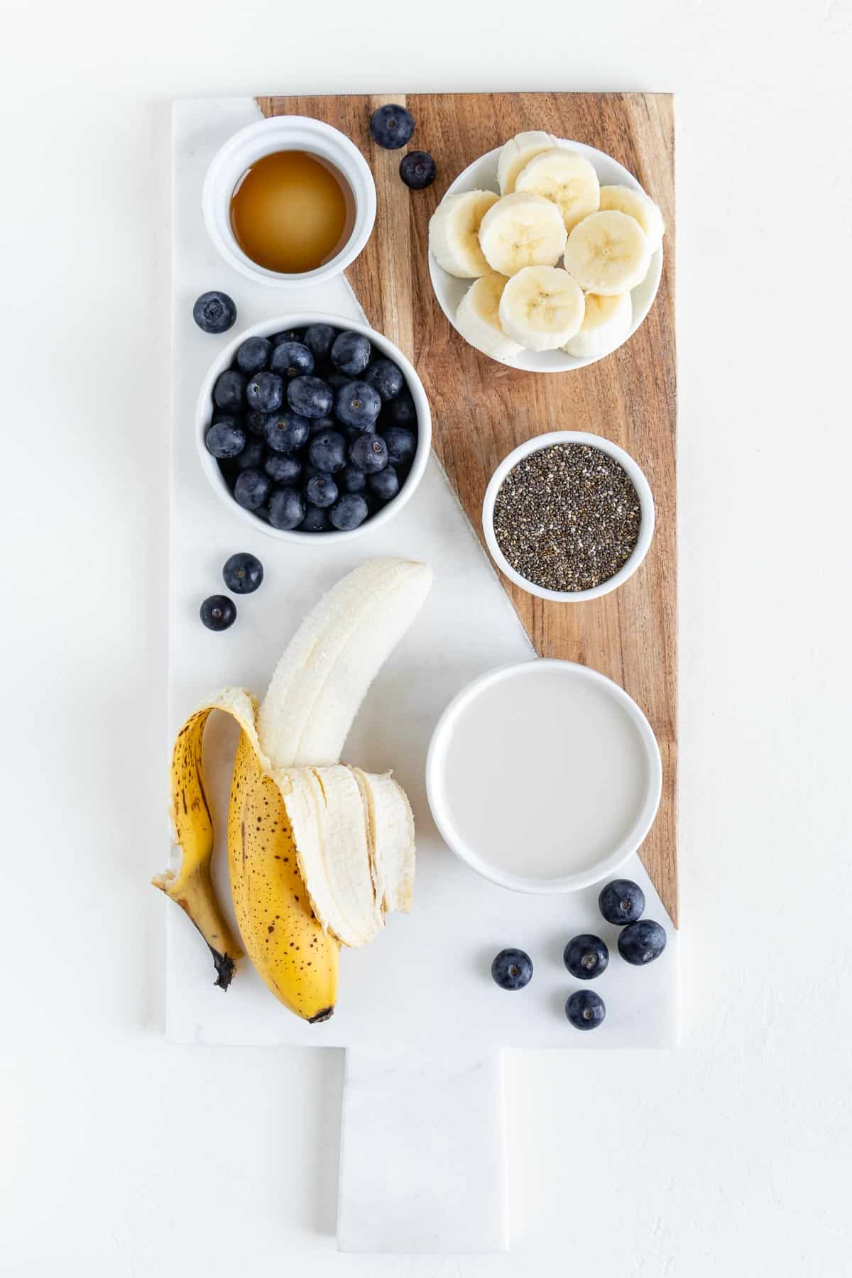 a ripe banana, a bowl of blueberries, a bowl of chia seeds, a glass of almond milk, and a bowl of sliced bananas on a marble cutting board