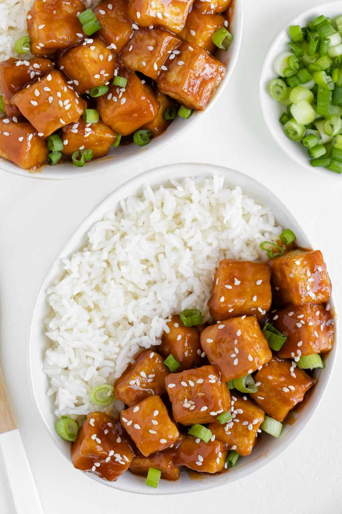 two bowls filled with white rice and crispy baked orange tofu