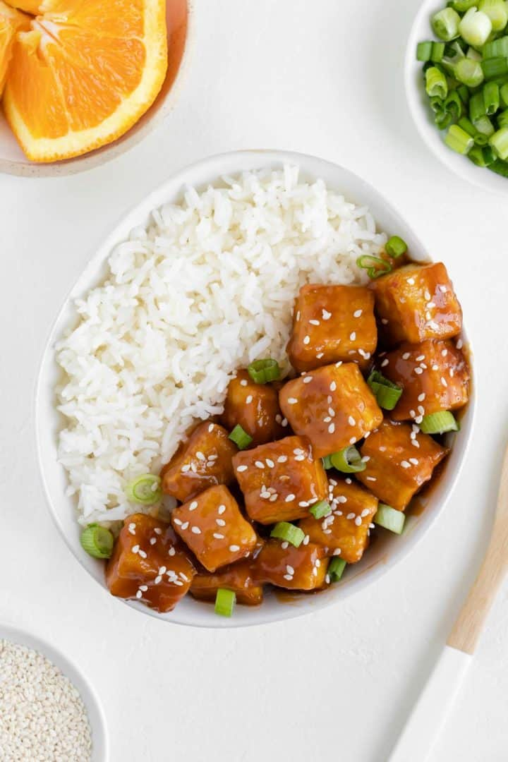 orange tofu in a bowl with white rice, surrounded by a plate of oranges, green onions, and sesame seeds