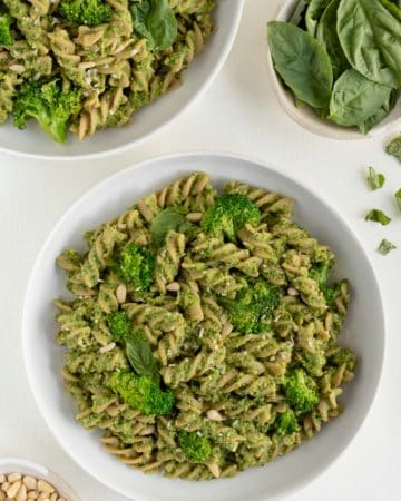 two bowls of vegan broccoli pesto pasta surrounded by a bowl of basil and a bowl of toasted pine nuts
