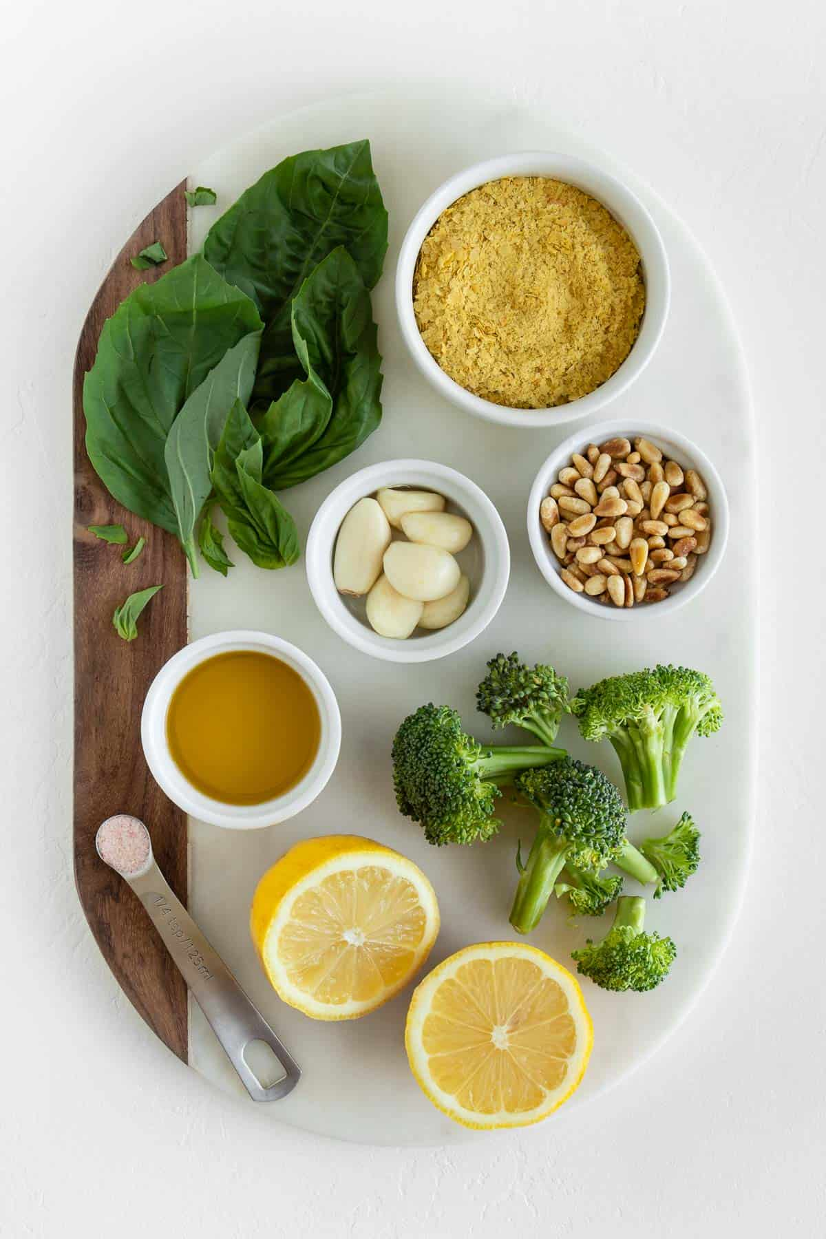 basil, pine nuts, garlic cloves, lemon, olive oil, nutritional yeast, and salt on a white marble board