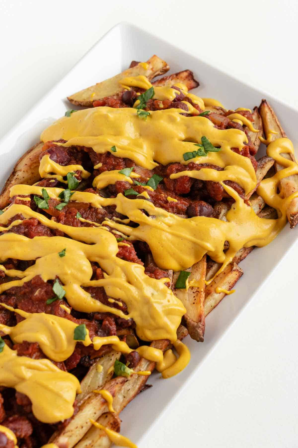 baked french fries topped with vegan chili and nacho cheese