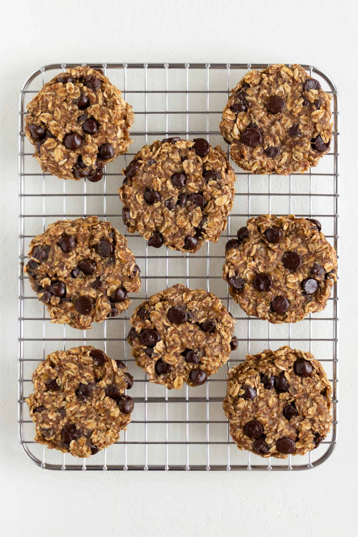 eight banana oatmeal chocolate chip cookies on a wire cooling rack