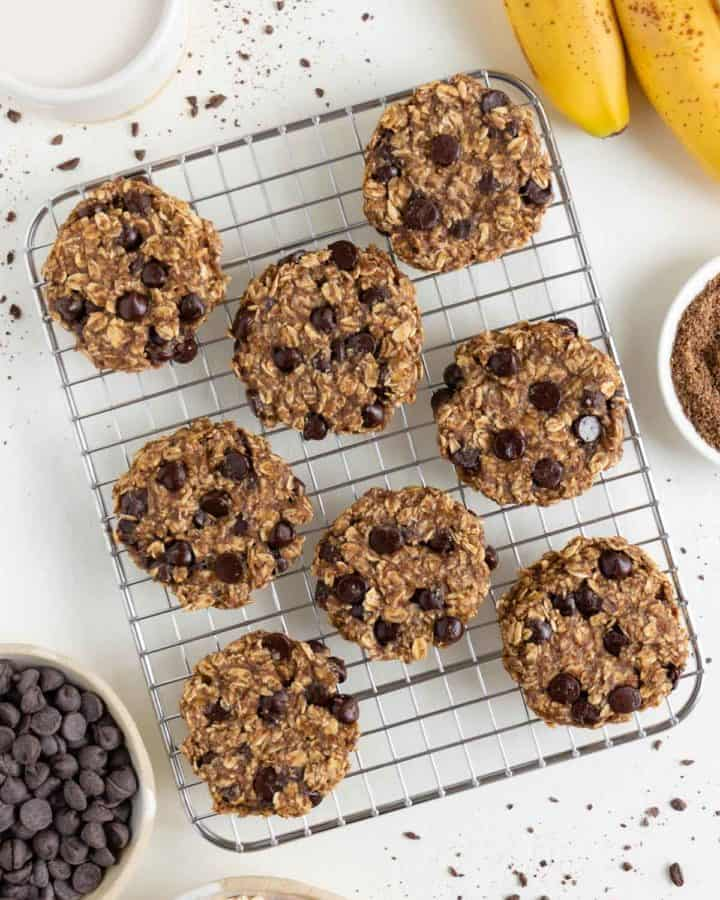 eight banana oatmeal chocolate chip cookies on a wire cooling rack surrounded by a bundle of bananas, oats, and a glass of almond milk
