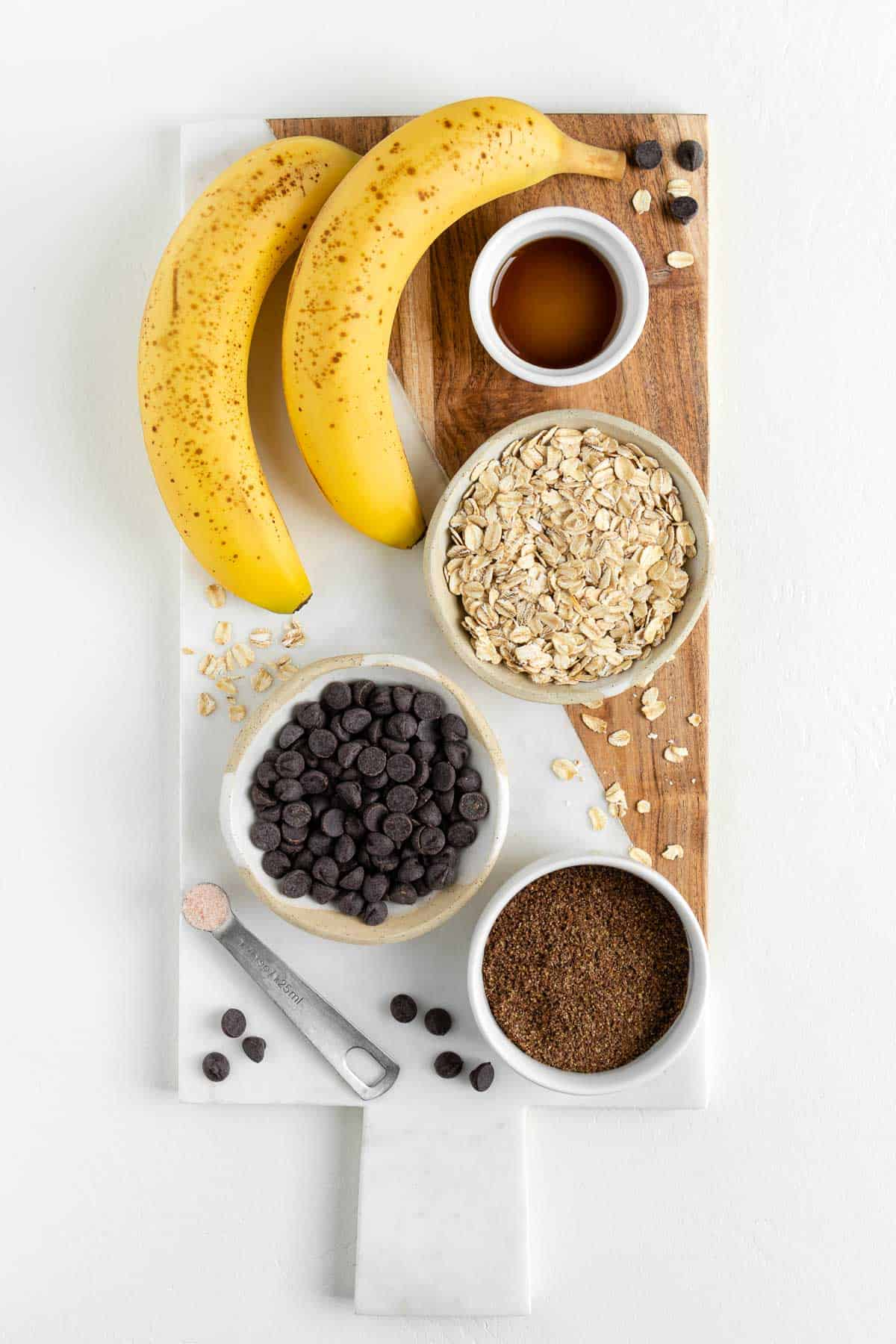 a white marble board topped with oats, vanilla, ground flaxseed, chocolate, and fruit