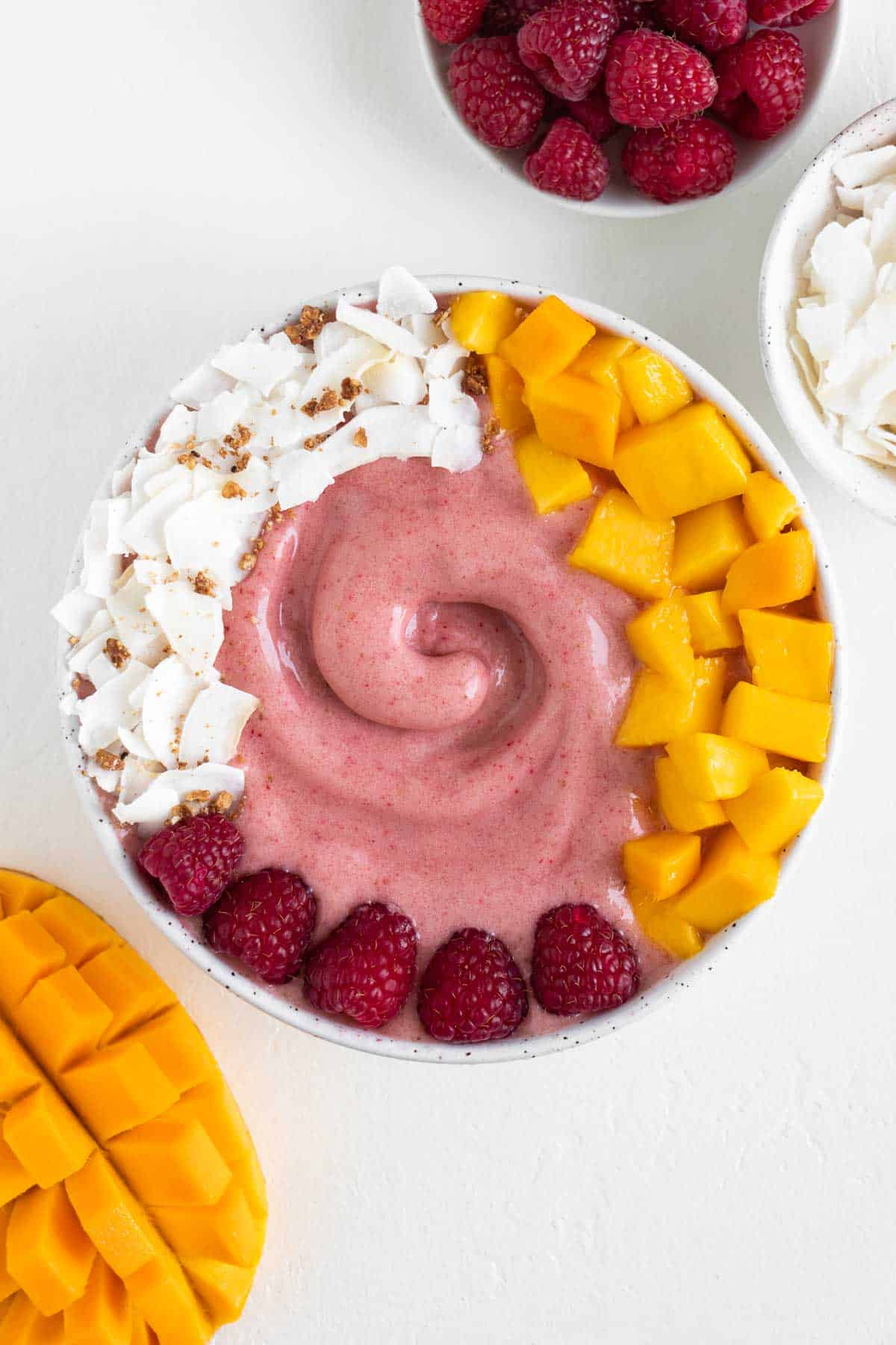 a raspberry mango smoothie bowl surrounded by a bowl of berries, a bowl of coconut, and a sliced mango