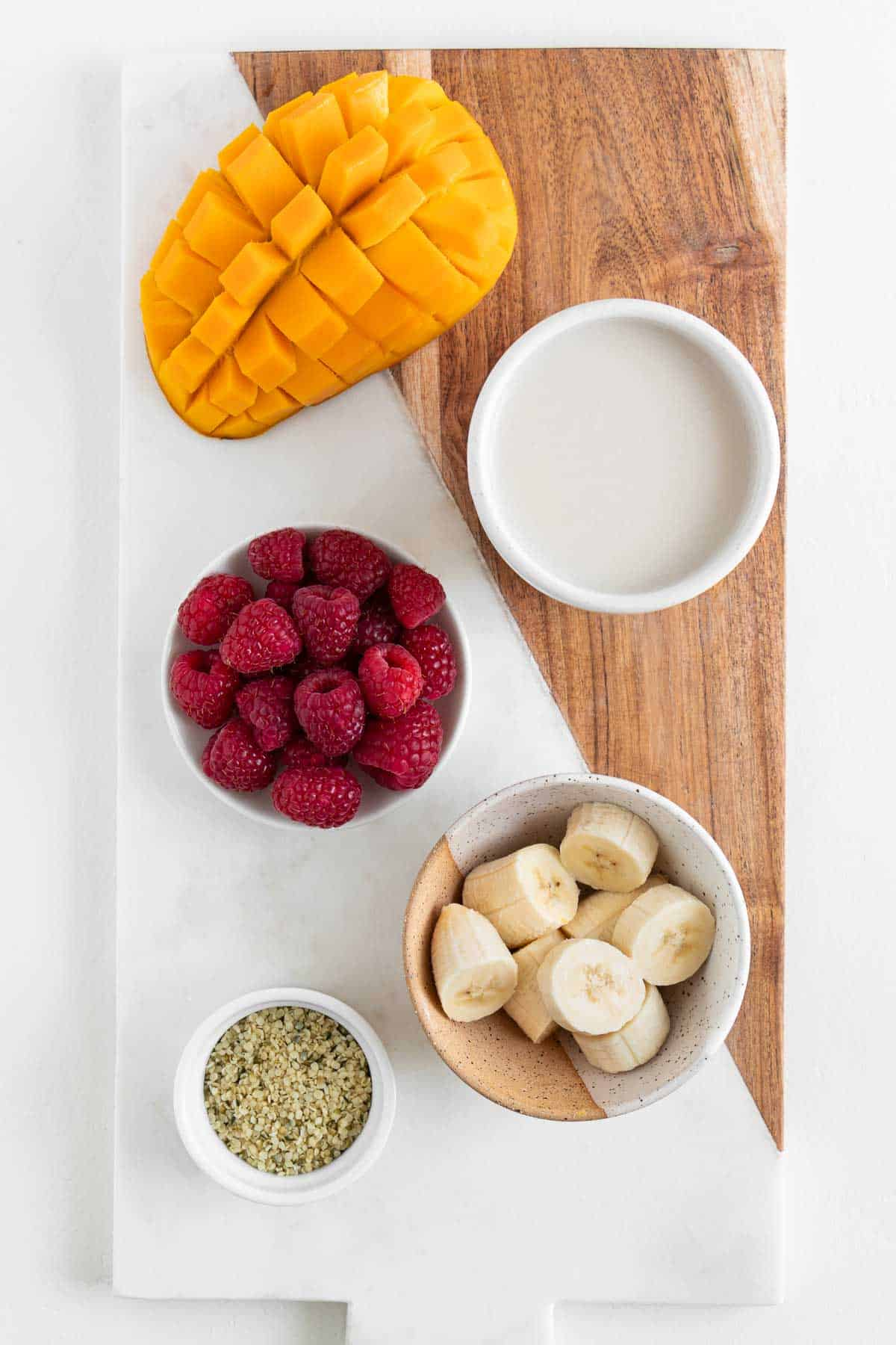 a marble and wood cutting board topped with a glass of coconut milk, bananas, berries, and hemp seeds