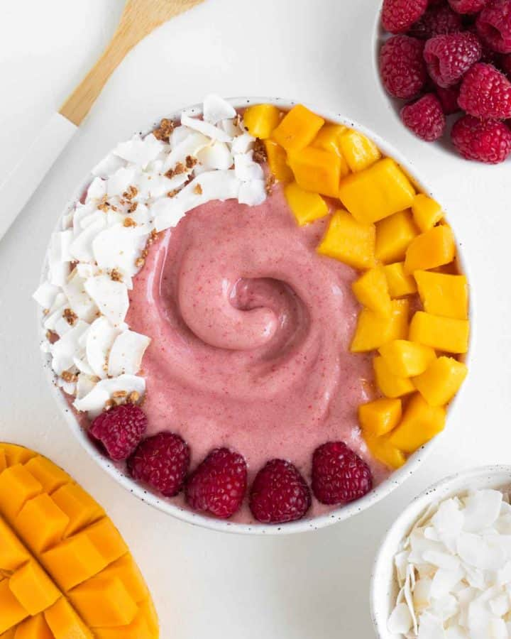 a pink raspberry mango smoothie bowl surrounded by a wooden fork and bowls of fruit