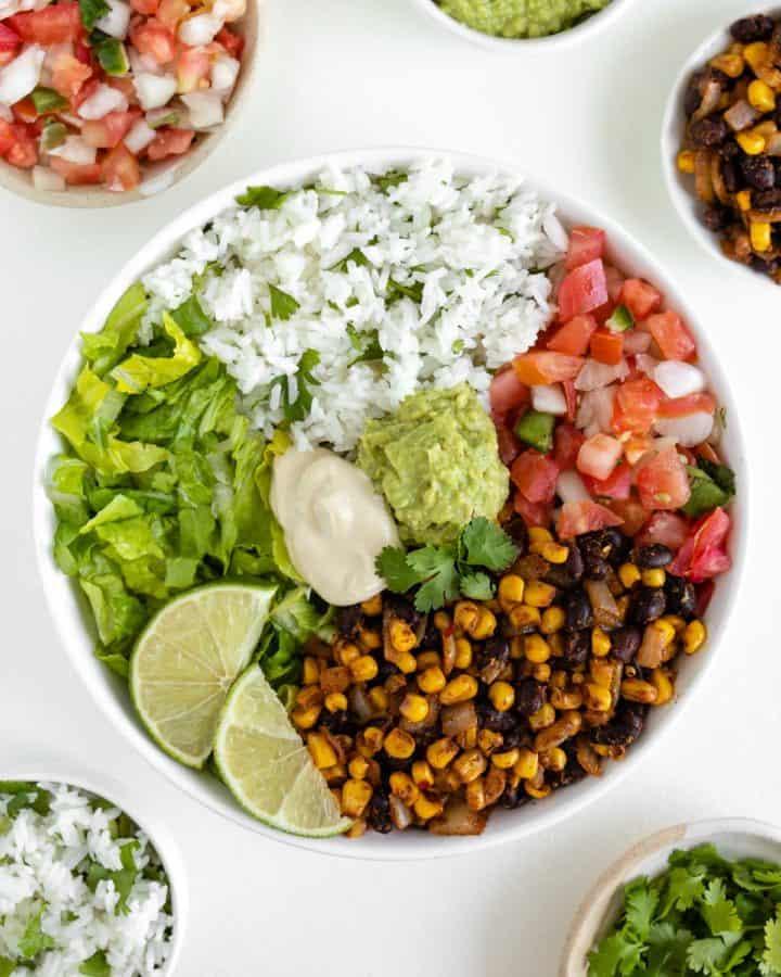 vegan burrito bowl with black beans, corn, cilantro lime rice, pico de gallo, lettuce, guacamole, and cashew sour cream