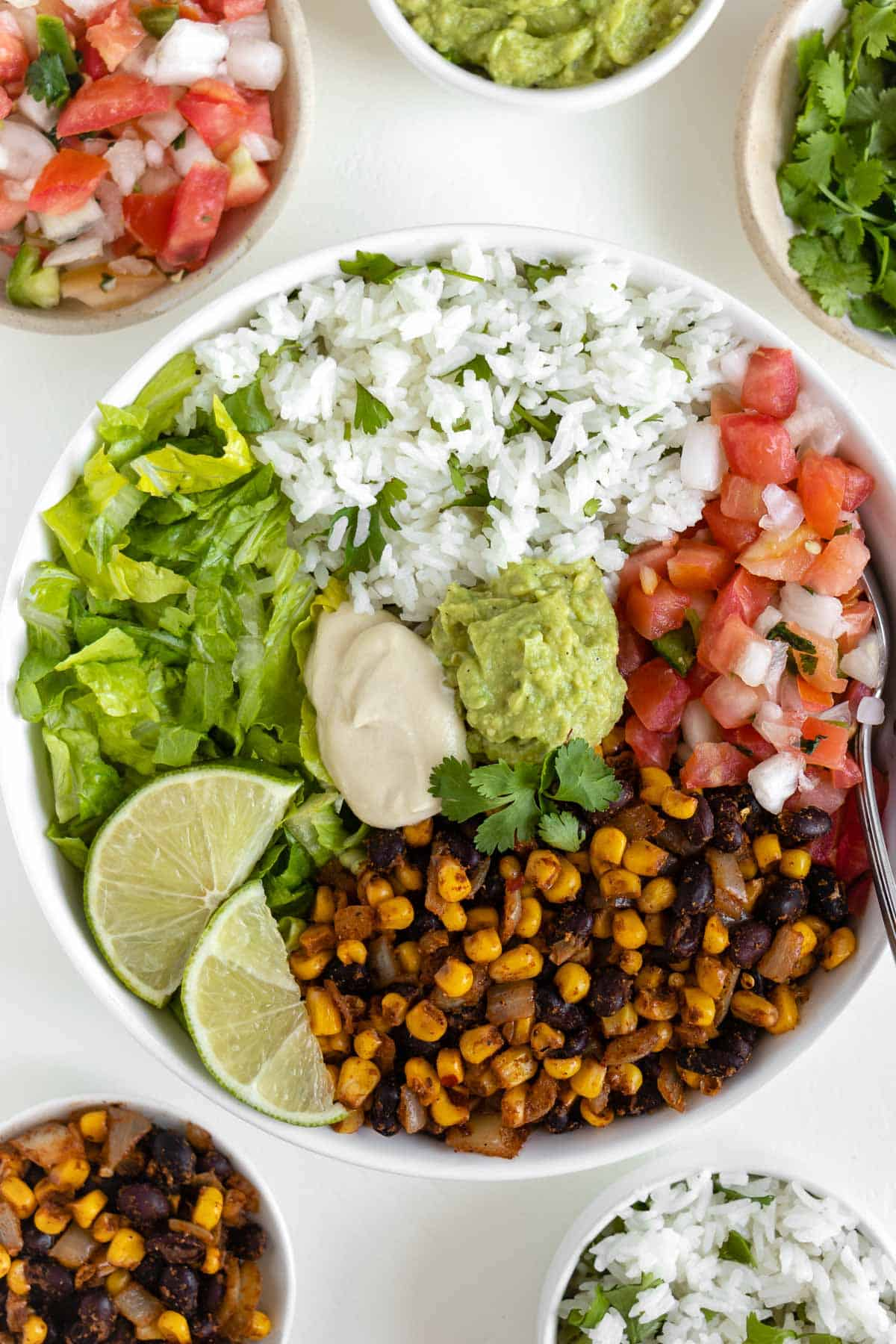 vegan burrito bowl with black beans, corn, cilantro lime rice, pico de gallo, lettuce, guacamole, and cashew sour cream