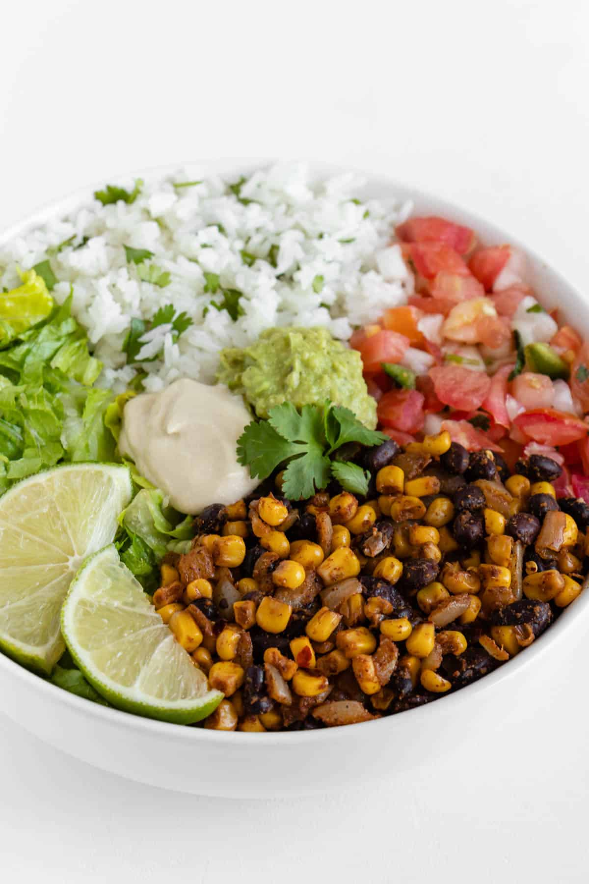 a vegan burrito bowl with cilantro lime rice, corn and beans, pico de gallo, guacamole, and romaine lettuce