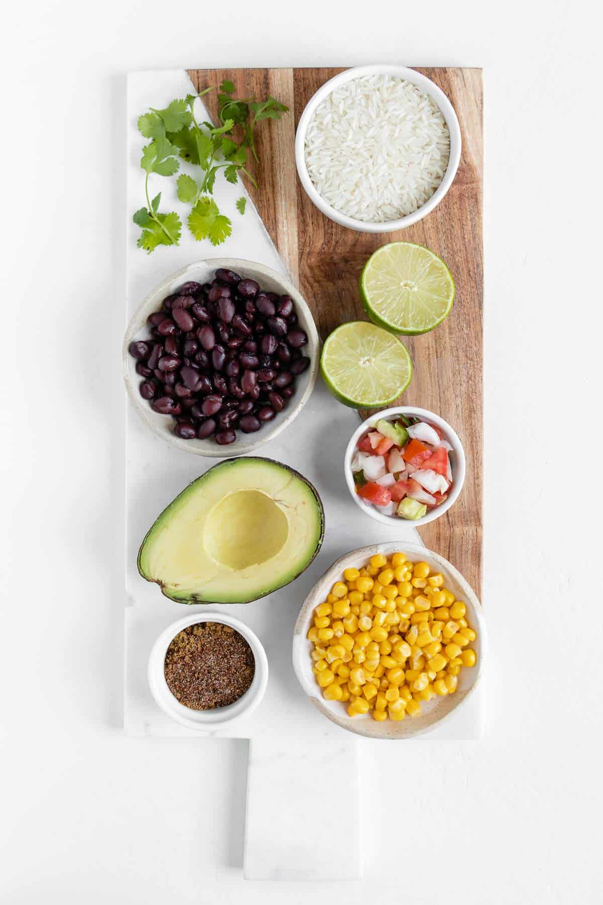 black beans, corn, diced onion, pico de gallo, avocado, spices, cilantro, and lime on a marble board