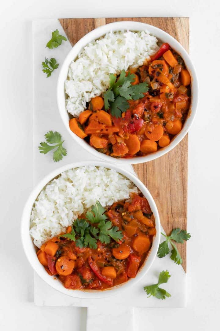 a wooden board topped with two bowls fo vegan thai red curry and rice