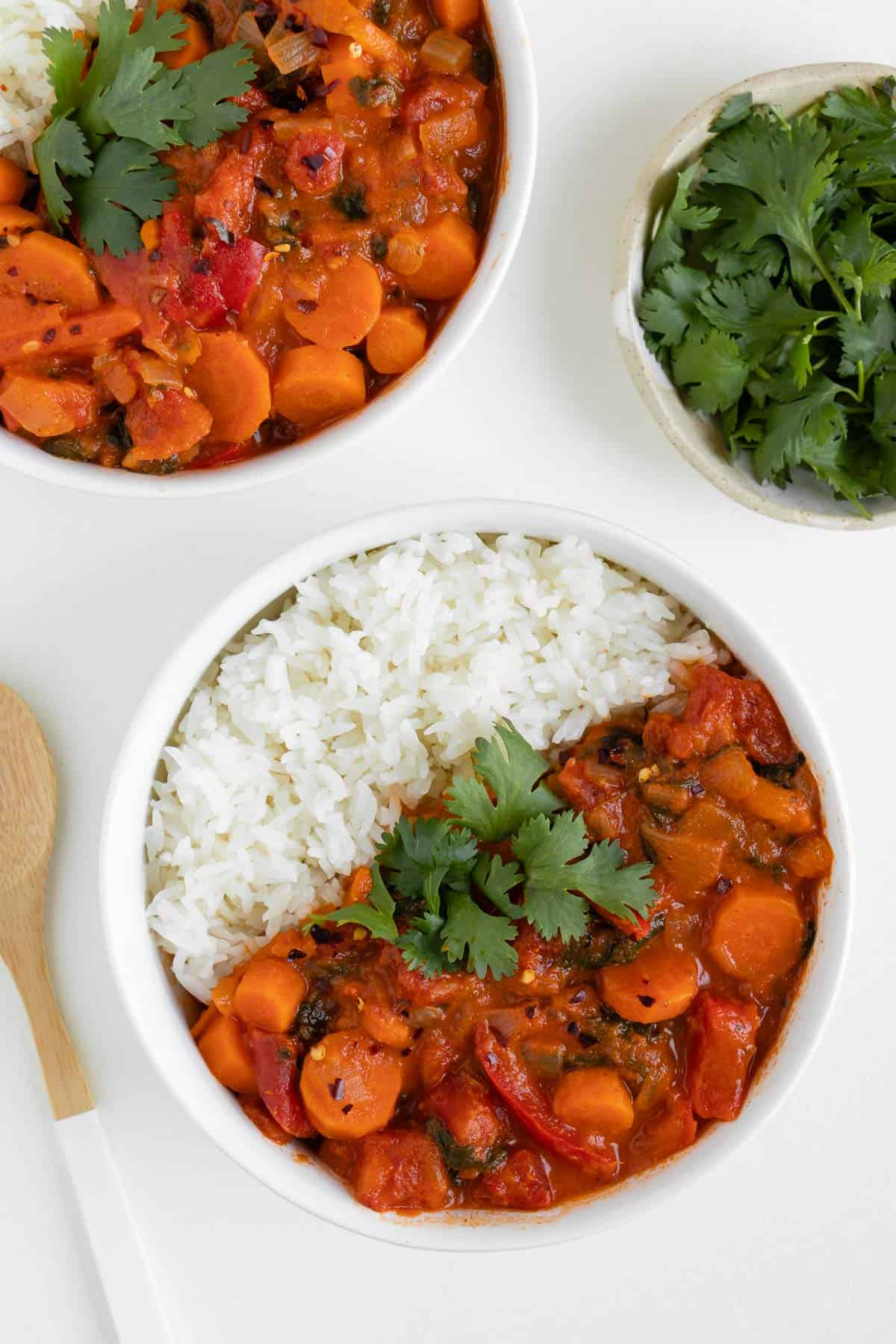 two white bowls filled with vegan thai red curry and white rice beside a bowl of cilantro