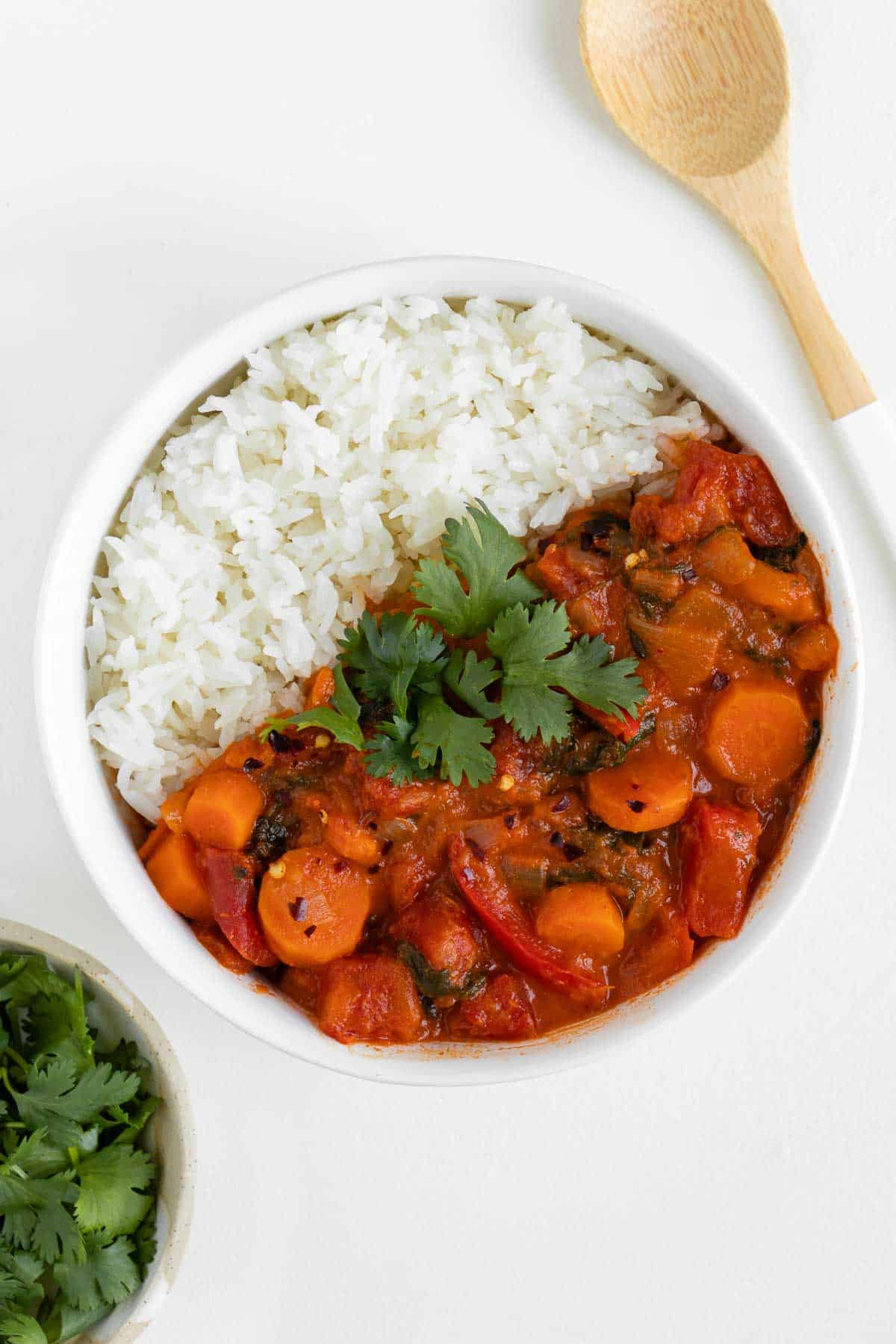 vegan thai red curry and white rice in a bowl alongside a wooden spoon and bowl of cilantro