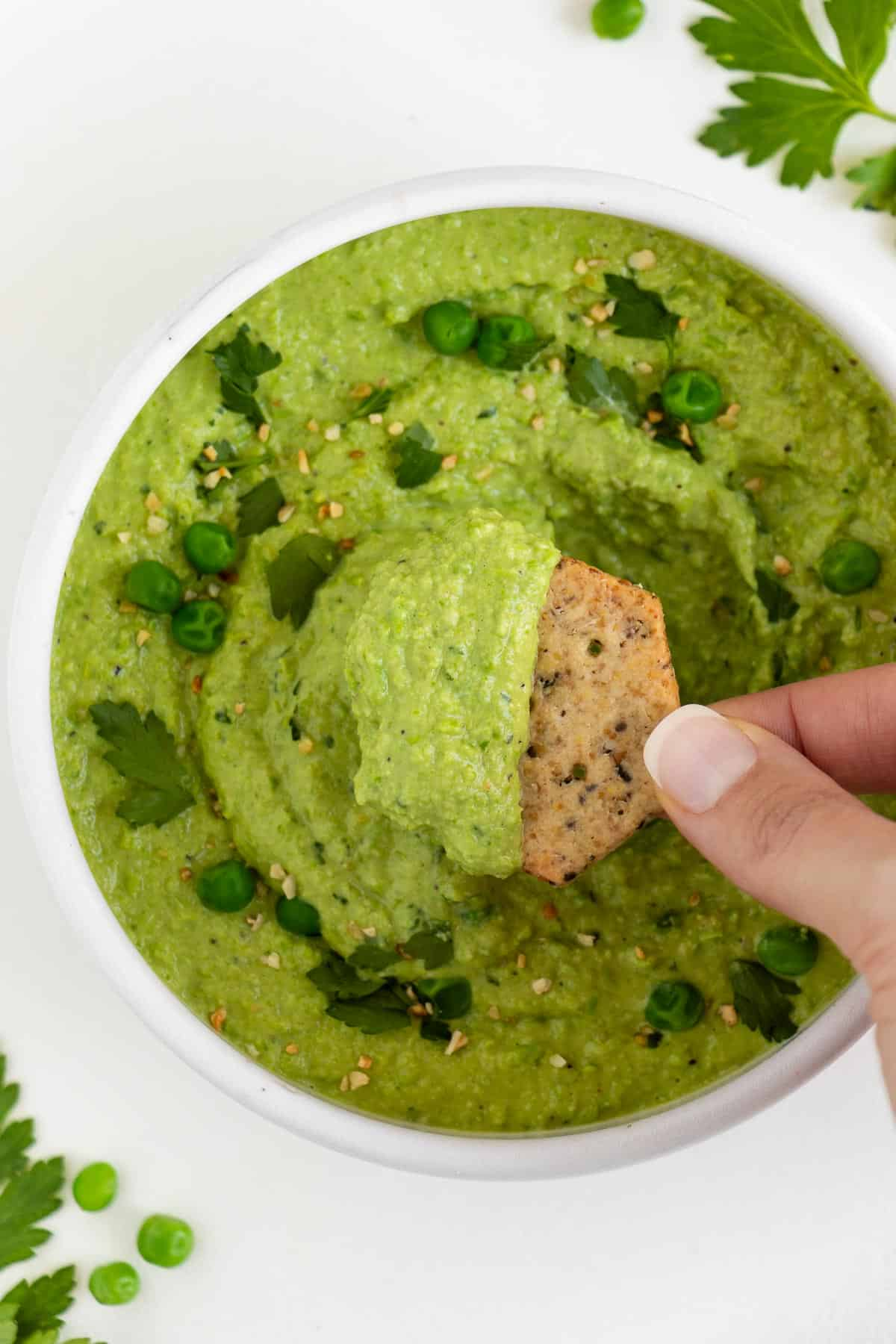a hand scooping a cracker into a bowl of green pea dip