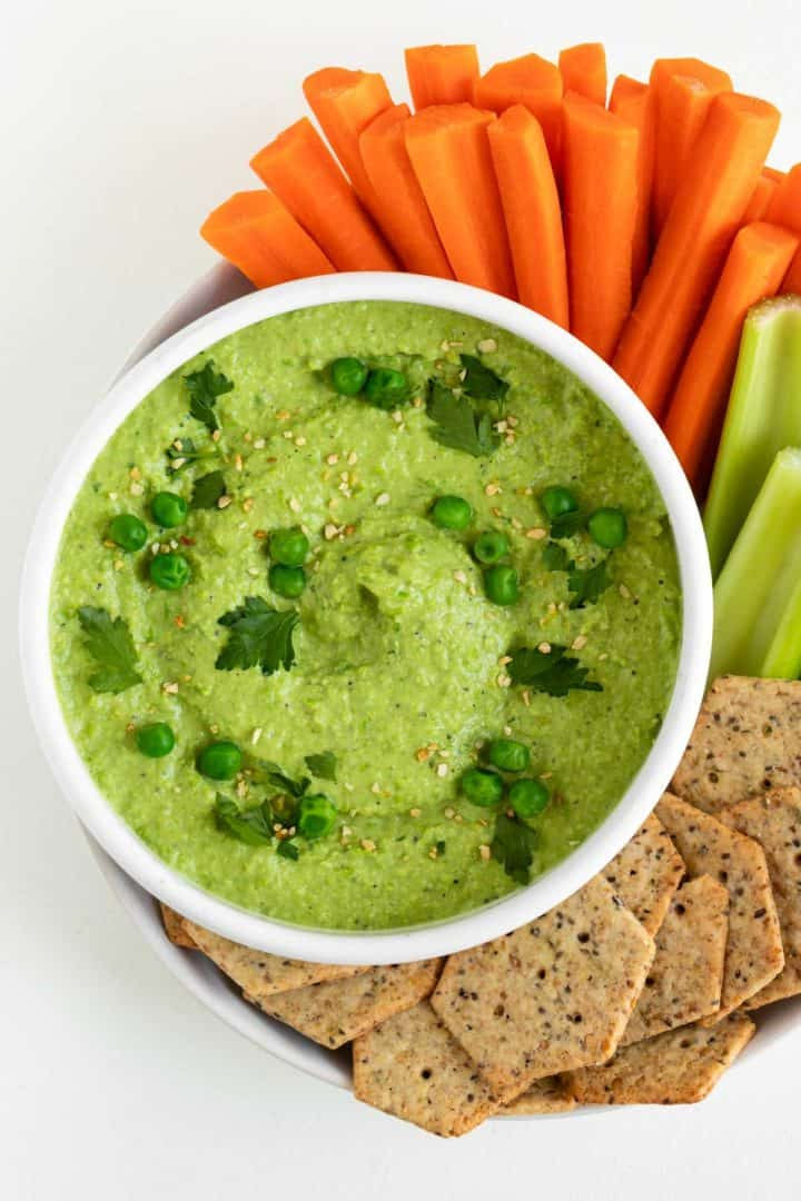 green pea hummus in a white bowl surrounded by sliced carrots, celery, and crackers