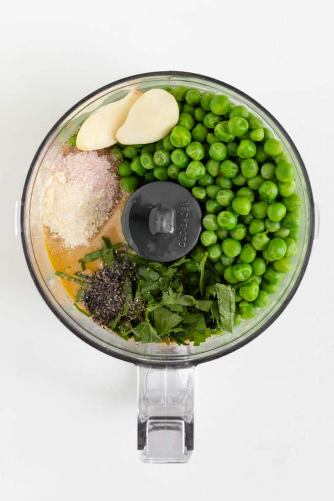 garlic, olive oil, tahini, salt, lemon juice, parsley, and peas inside a food processor