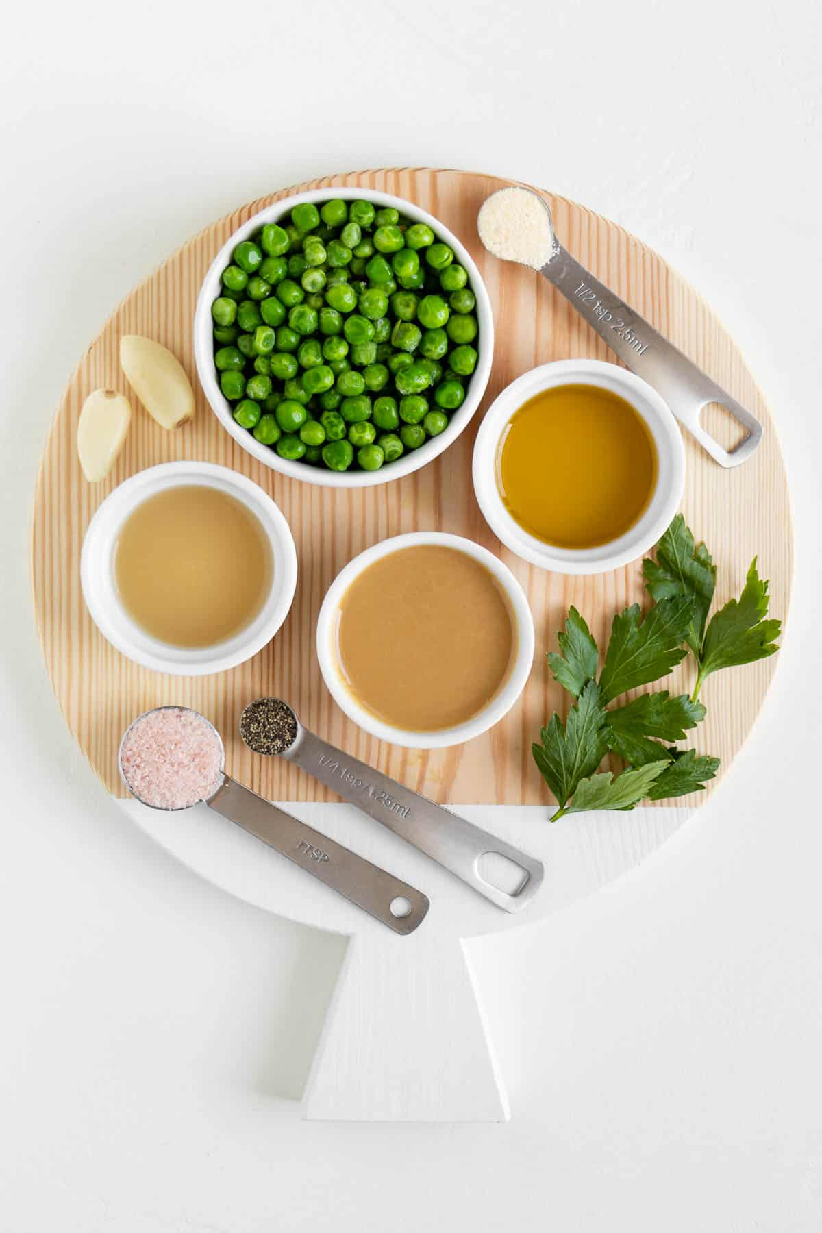 a circular wood cutting board topped with lemon juice, parsley, olive oil, tahini, garlic, peas, salt, and pepper