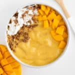 a mango turmeric smoothie bowl alongside a bamboo spoon and sliced mango