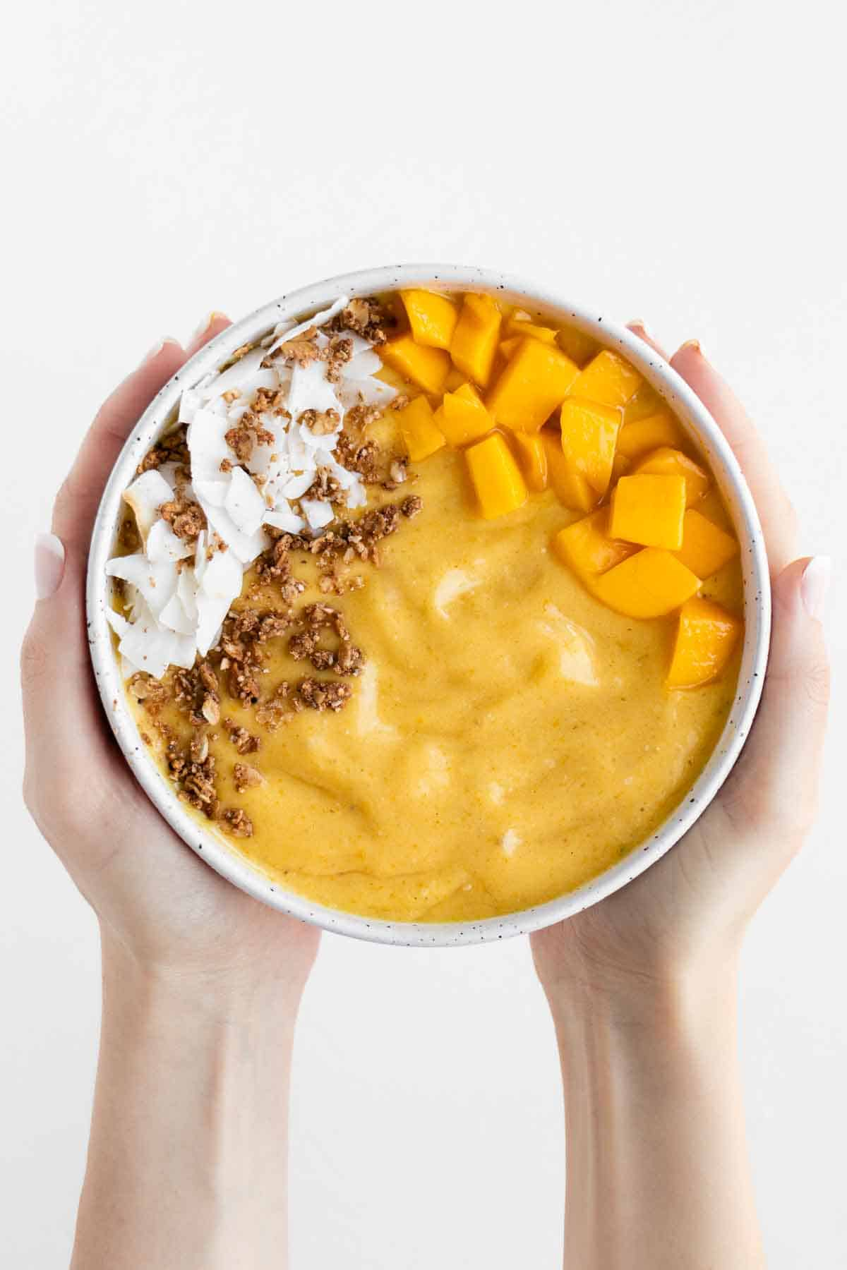 two hands holding a mango smoothie bowl topped with coconut flakes and granola