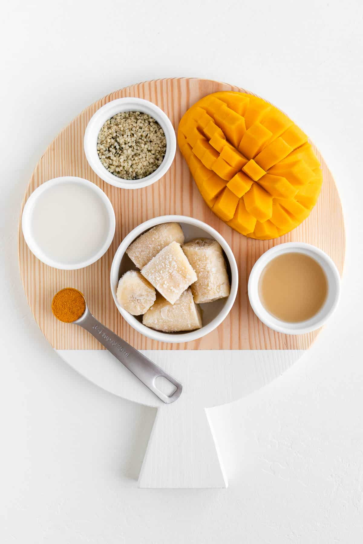a round wooden cutting board topped with fruit, lemon juice, turmeric powder, hemp seeds, and coconut milk
