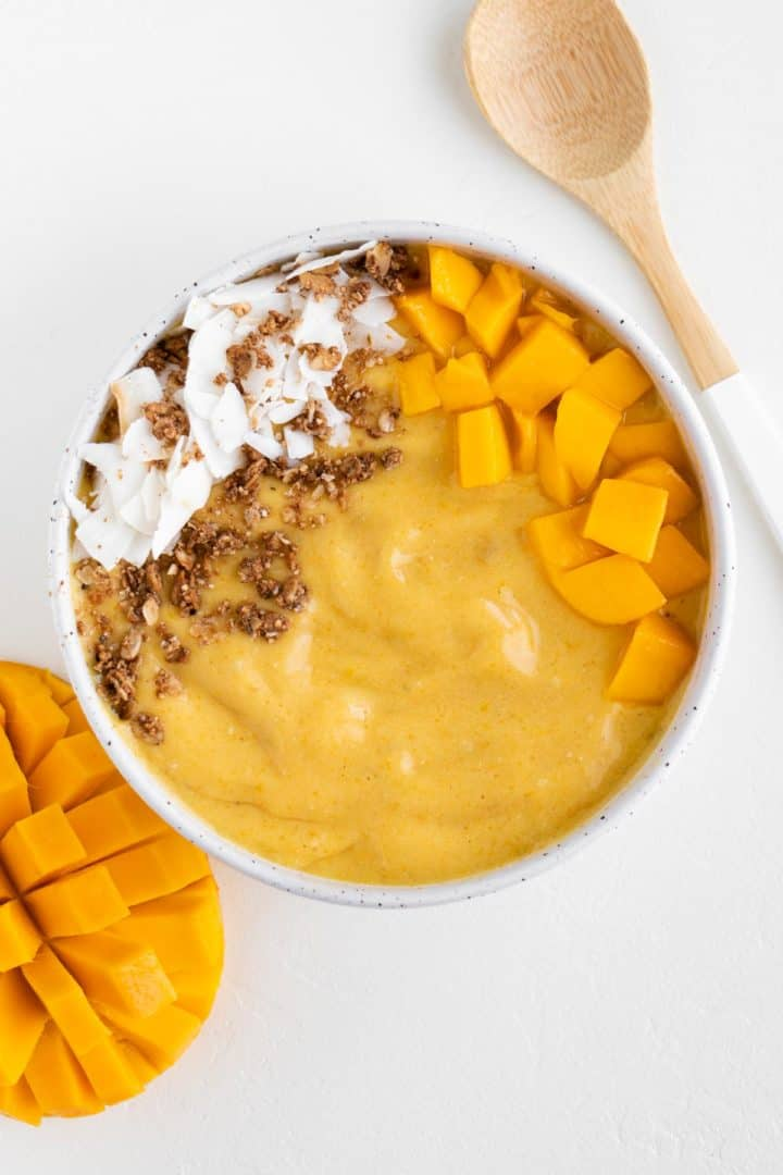 a mango turmeric smoothie bowl alongside a bamboo spoon and sliced mango