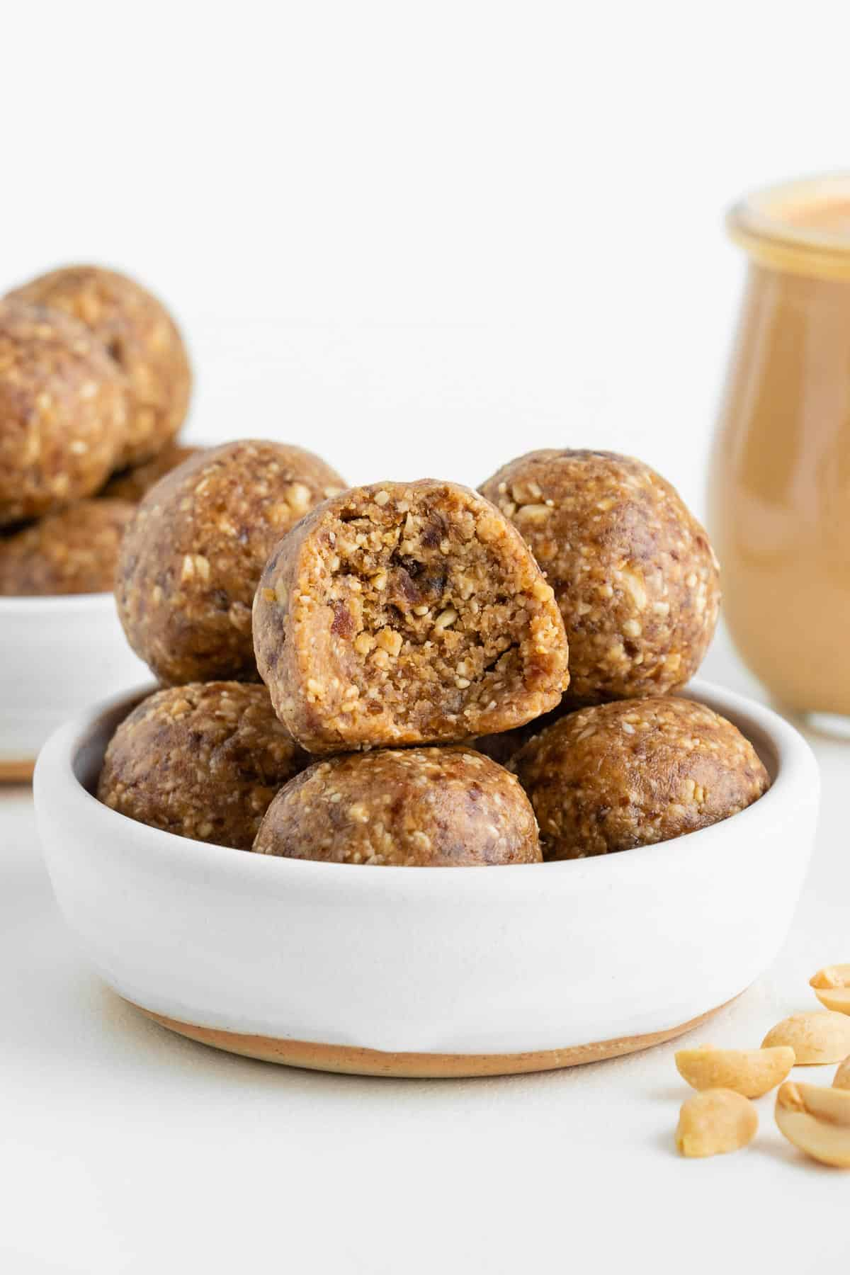 peanut butter energy balls stacked inside a white ceramic bowl with a bite taken out of the center ball