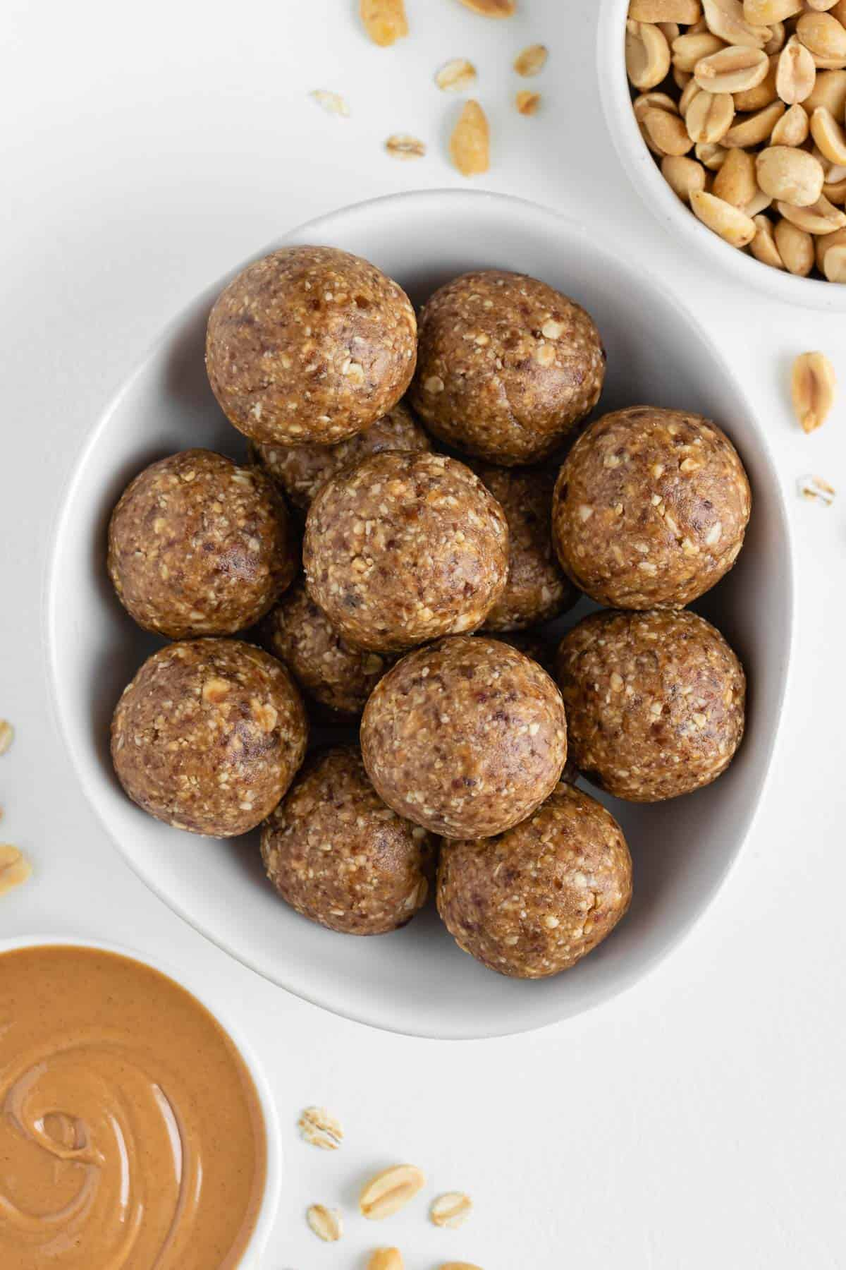 peanut butter energy balls stacked inside a white bowl surrounded by a bowl of peanut butter and a bowl of nuts