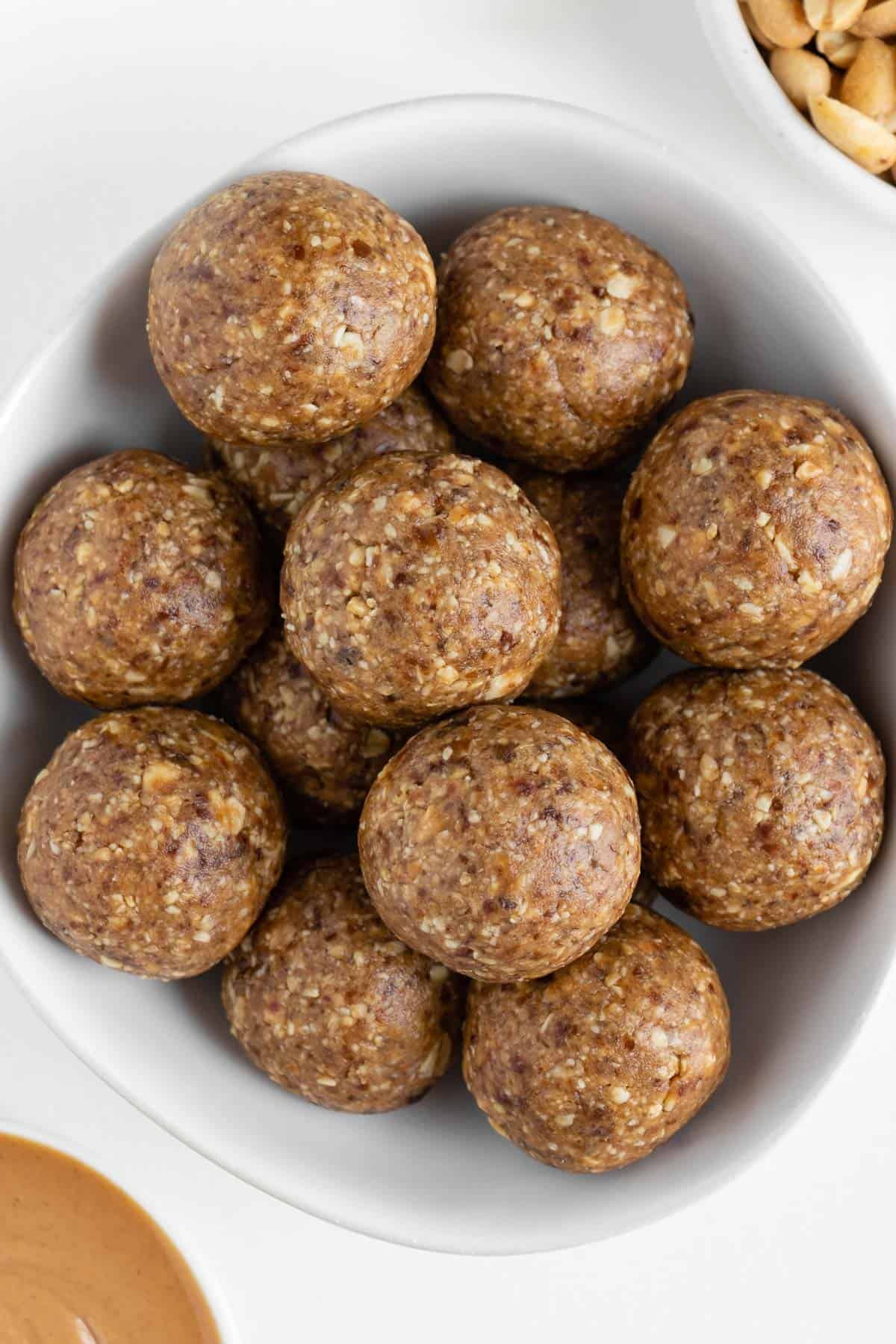 peanut butter energy balls stacked inside a white bowl