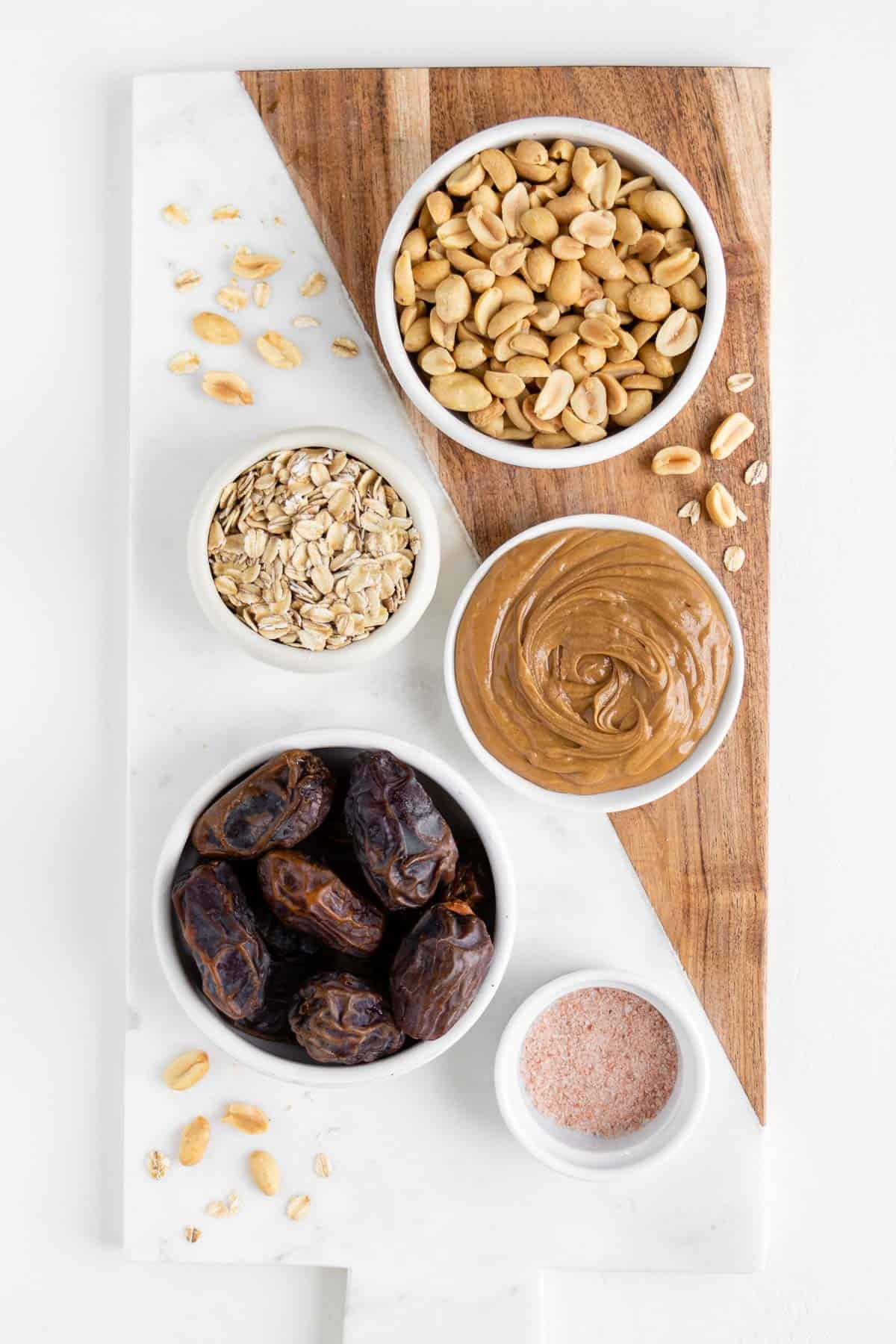 medjool dates, peanuts, oats, salt, and nut butter on a wooden marble cutting board