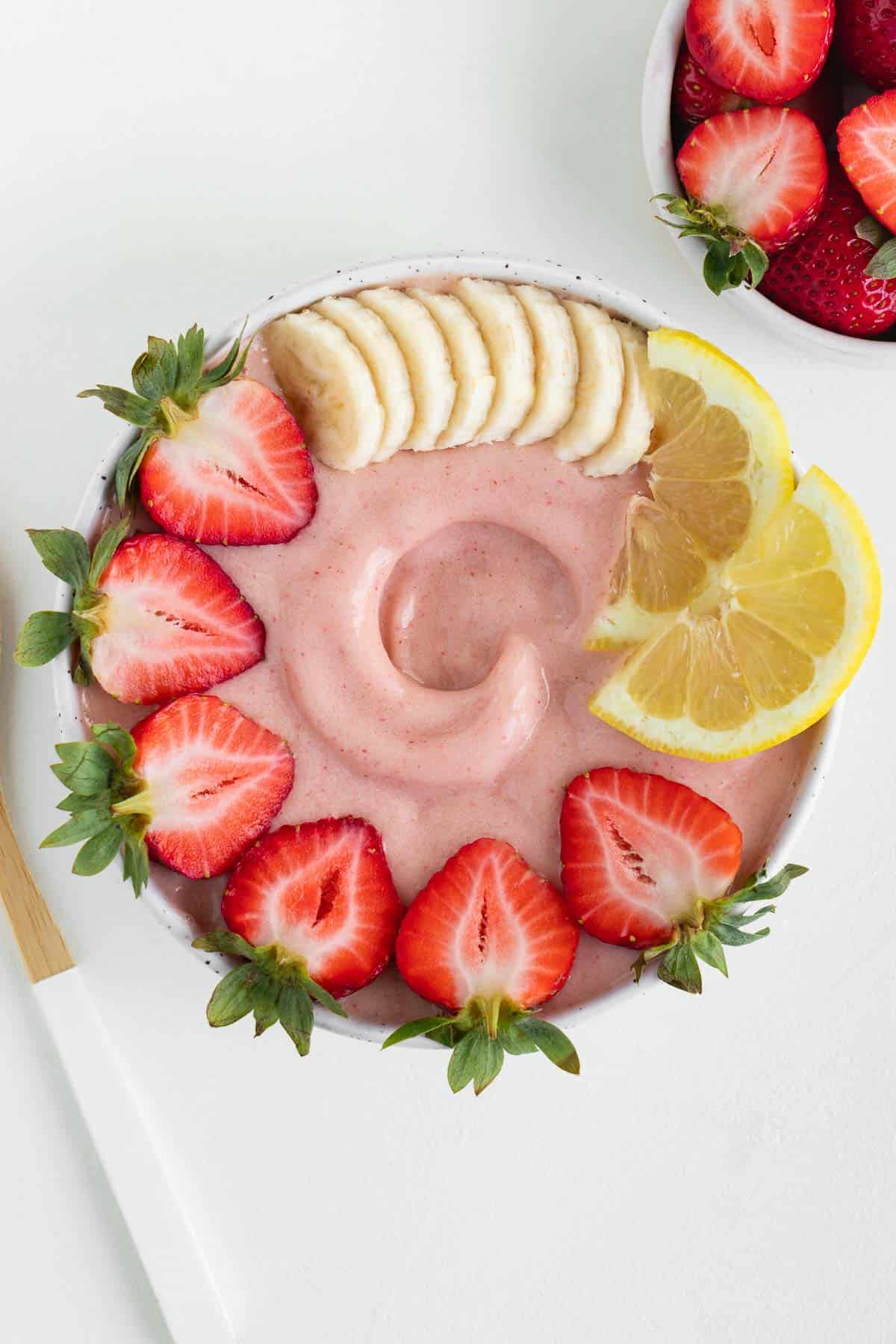 a strawberry lemonade smoothie inside a bowl topped with banana, berries, and sliced lemon