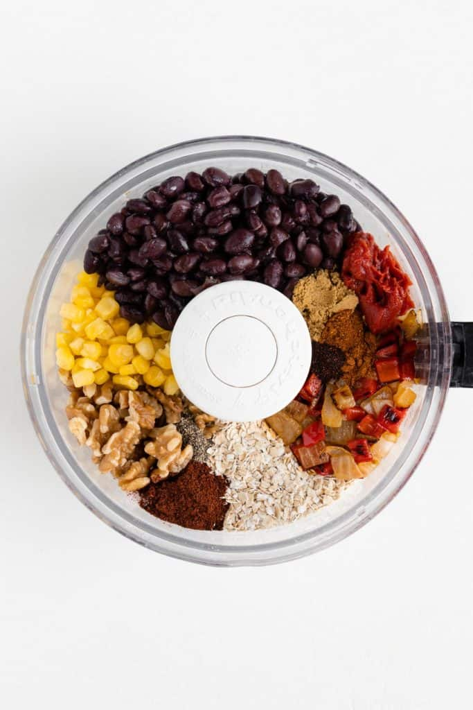 black beans, walnuts, corn, peppers, onions, oats, and spices inside the bowl of a food processor