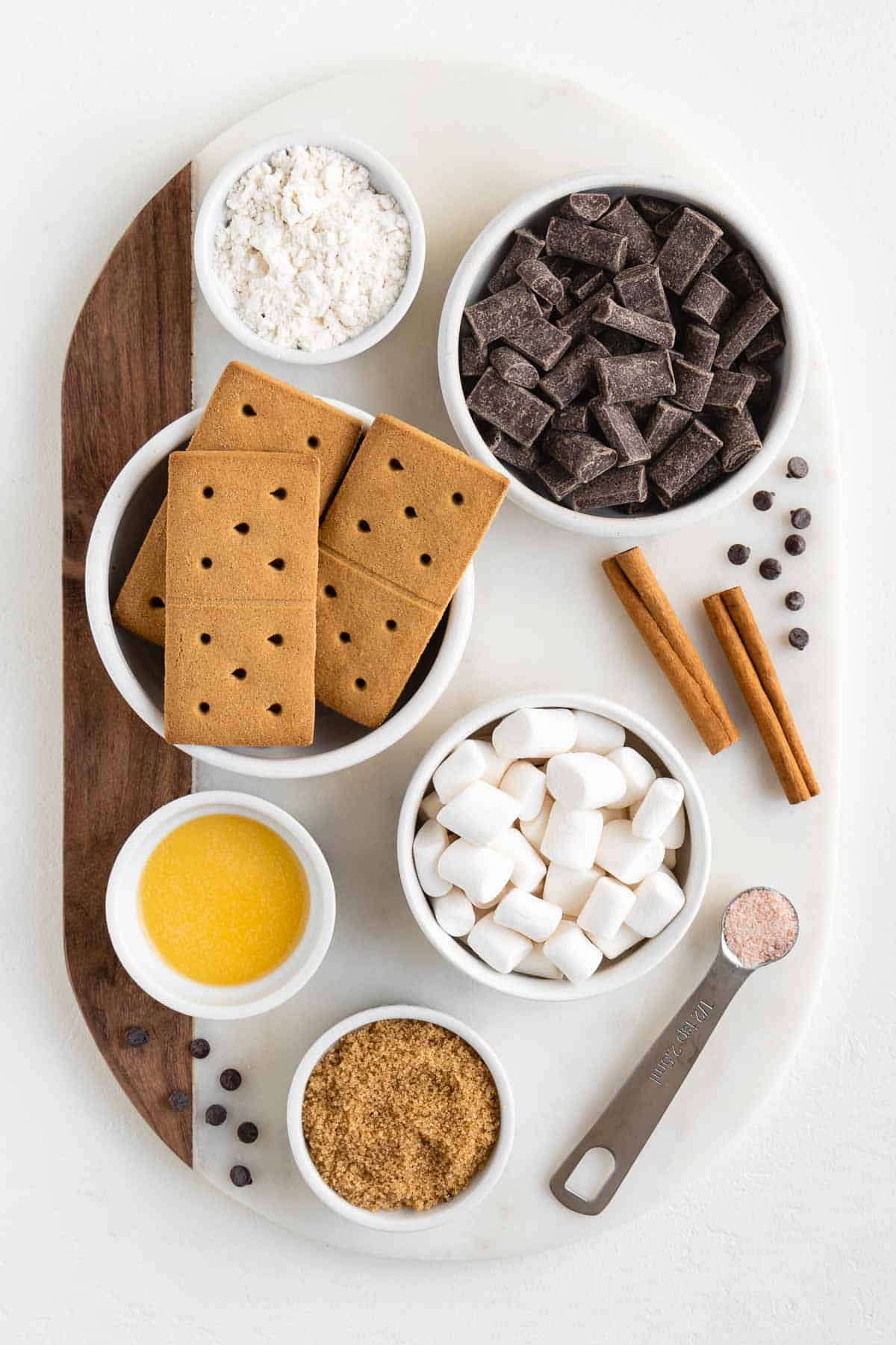 a marble cutting board topped with bowls of graham crackers, chocolate chunks, mini marshmallows, brown sugar, vegan butter, cinnamon sticks, flour, and salt