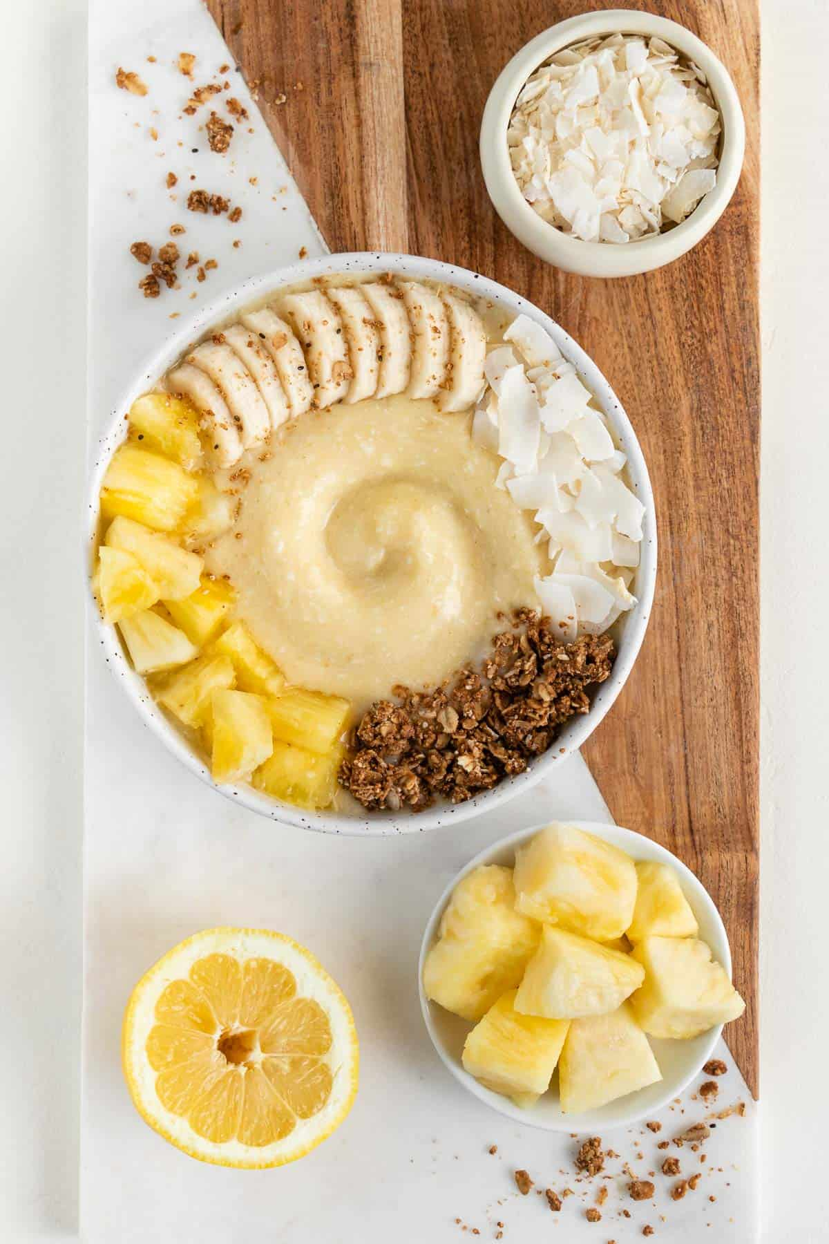 a wood and marble board topped with a piña colada smoothie bowl, bowl of coconut flakes, bowl of pineapple, and a lemon