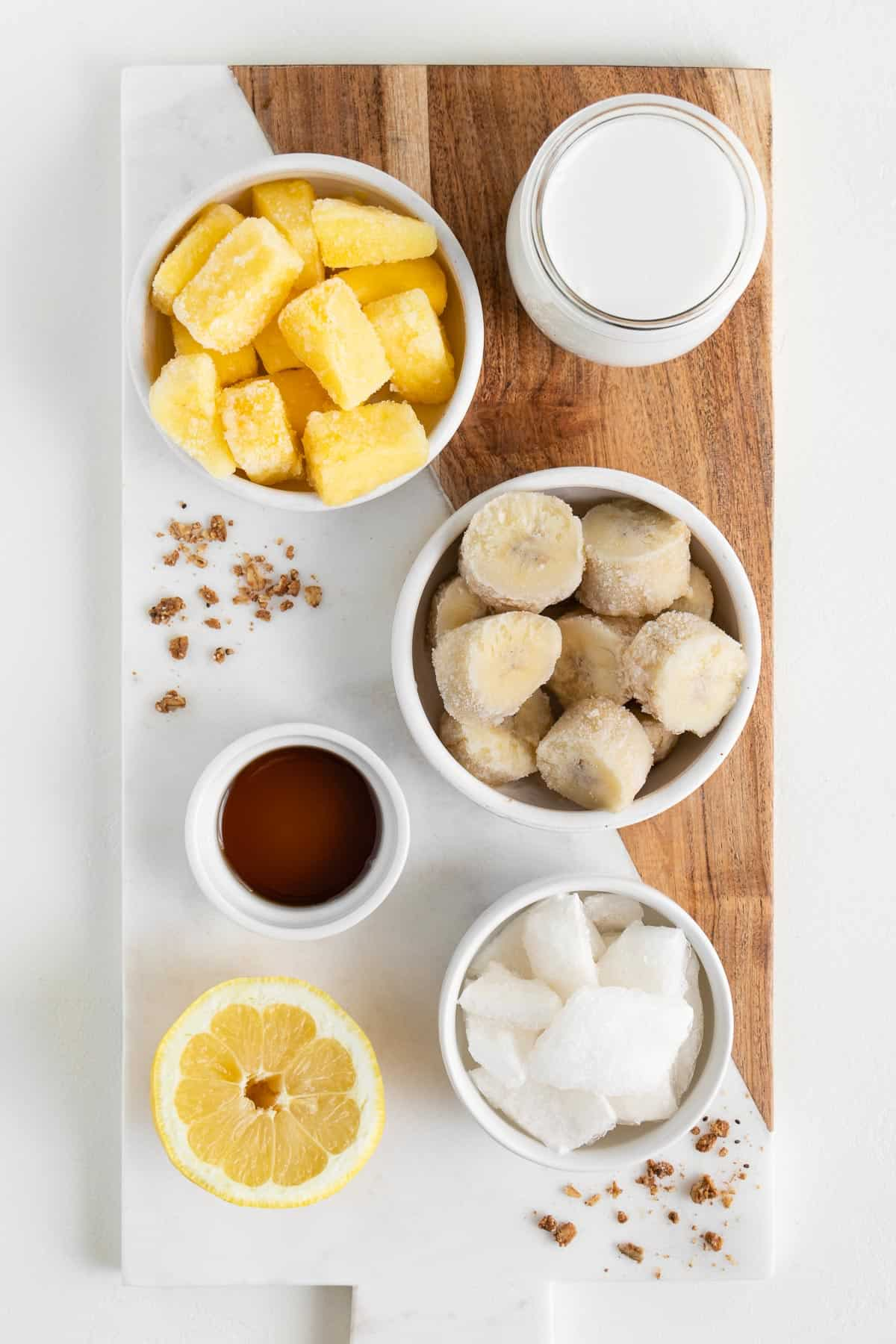 a marble wooden board topped with bananas, pineapple, maple syrup, lemon juice, coconut chunks, coconut milk, and a lemon