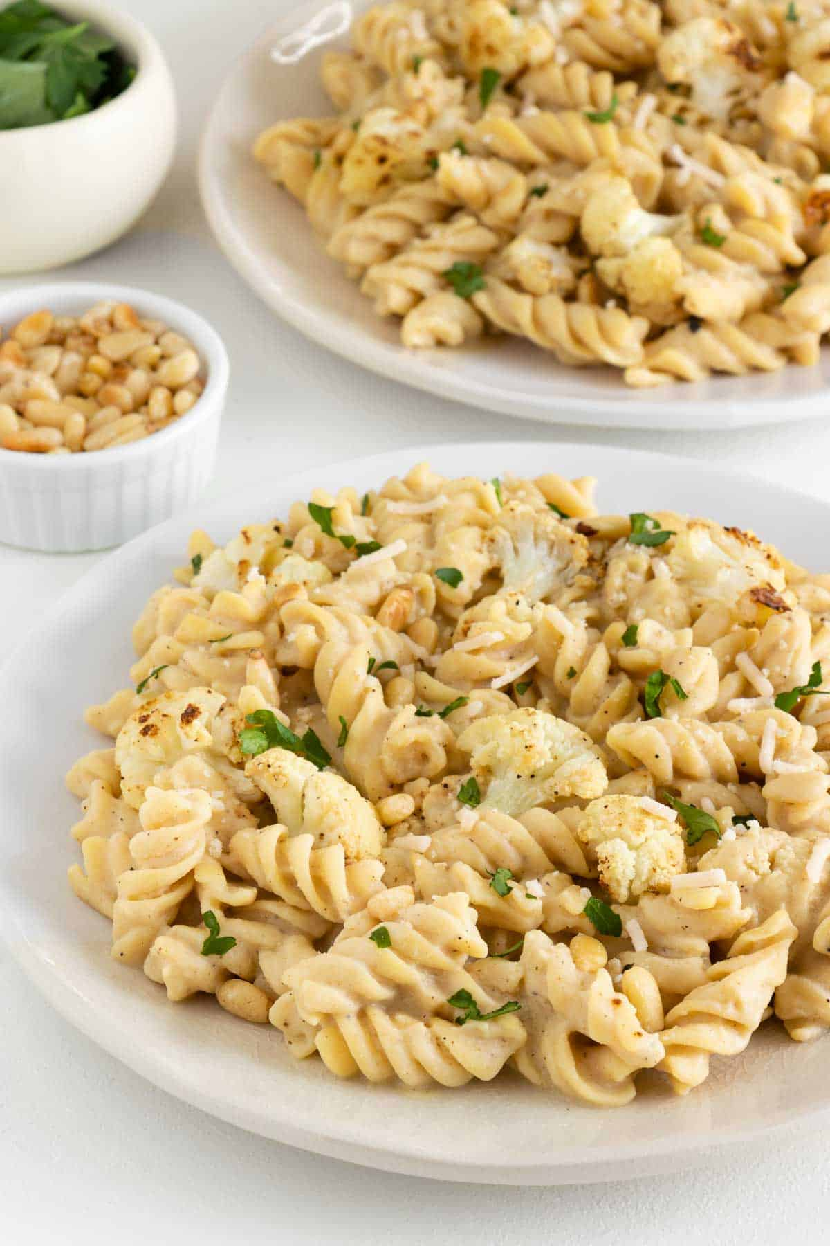 vegan roasted cauliflower alfredo pasta on two plates beside a bowl of pine nuts and fresh parsley