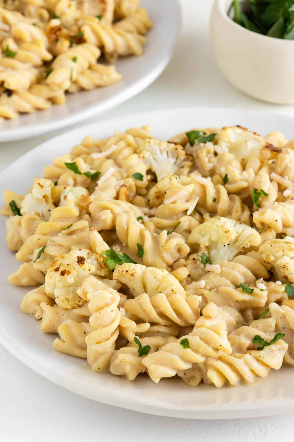 vegan roasted cauliflower alfredo pasta tossed with parsley, pine nuts, and parmesan cheese