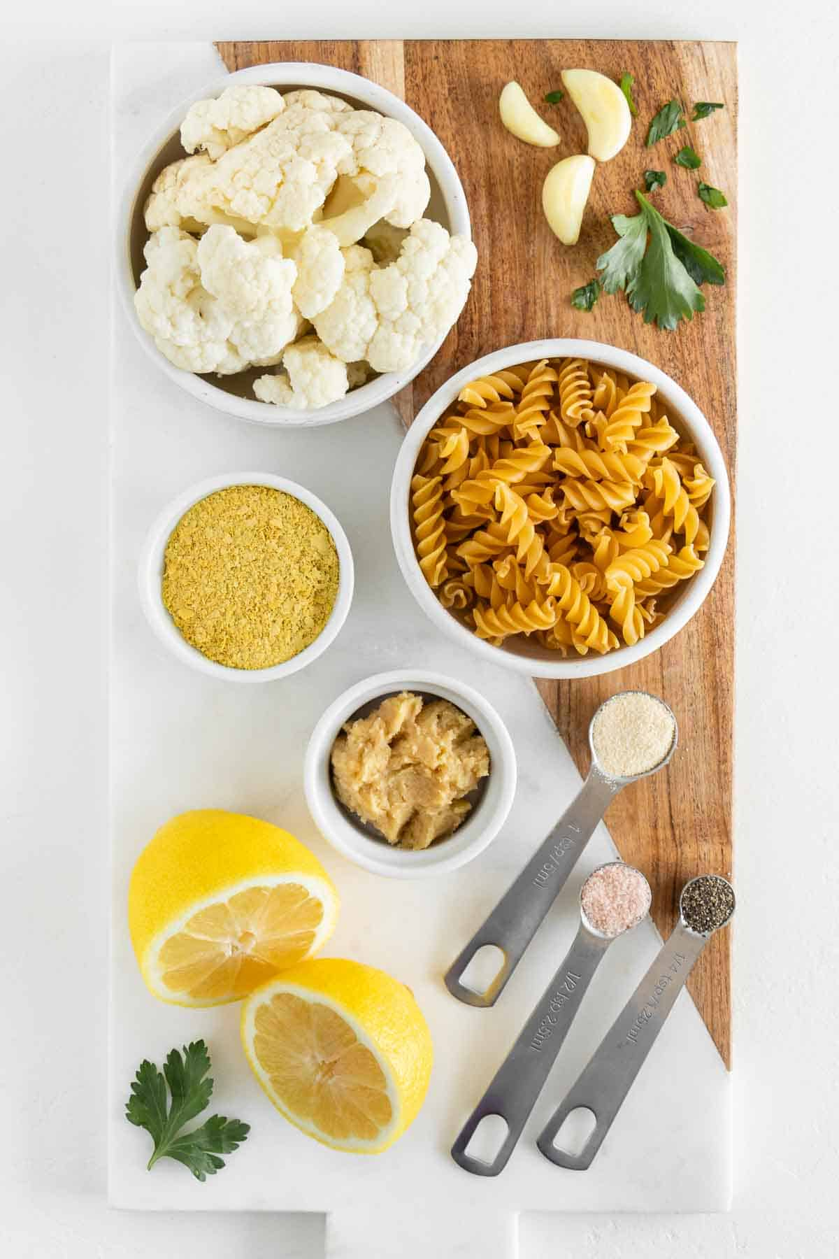 a marble board topped with cauliflower florets, nutritional yeast, rotini pasta shells, sliced lemon, parsley, garlic cloves, and mellow white miso paste