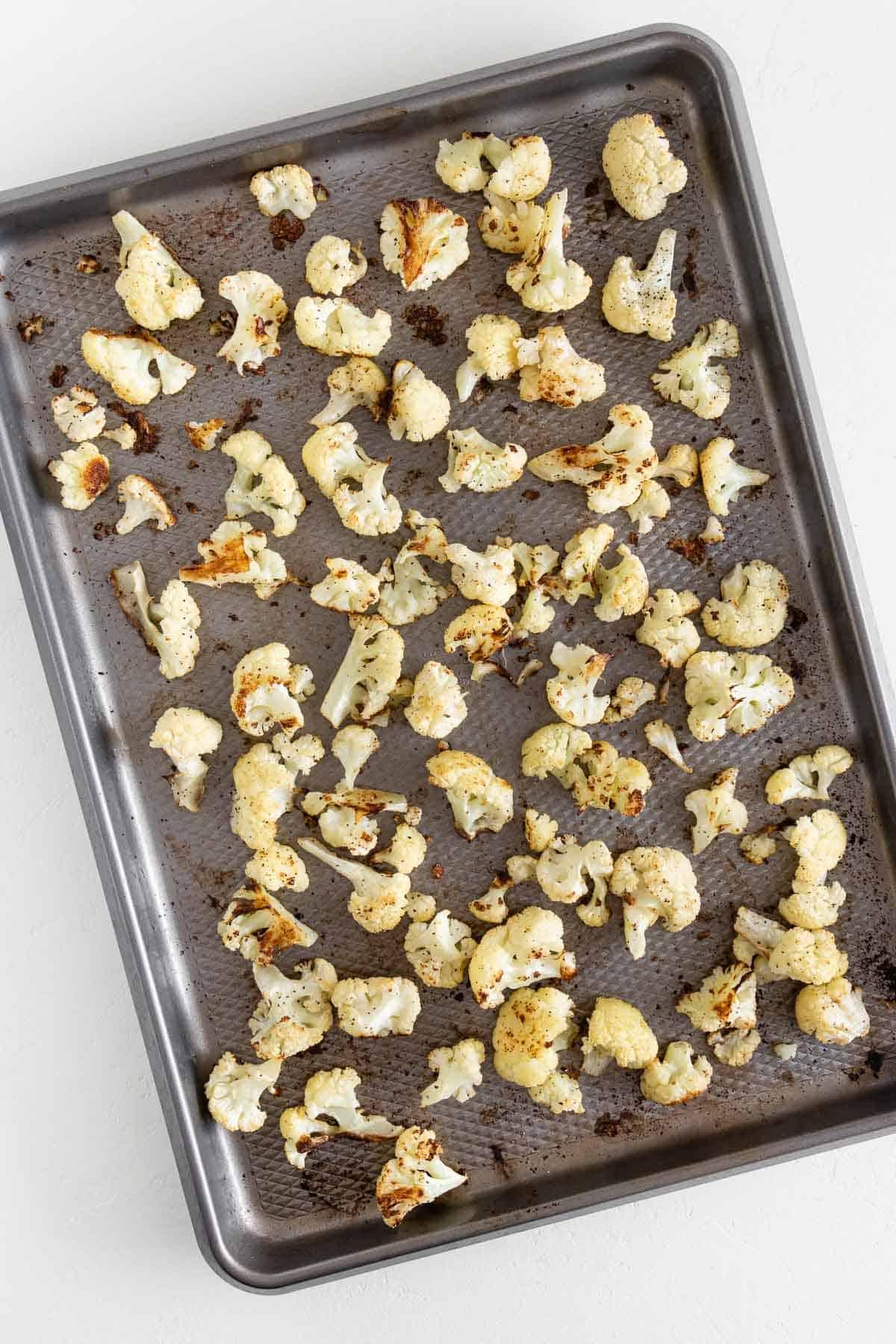 roasted cauliflower florets spread across a baking sheet