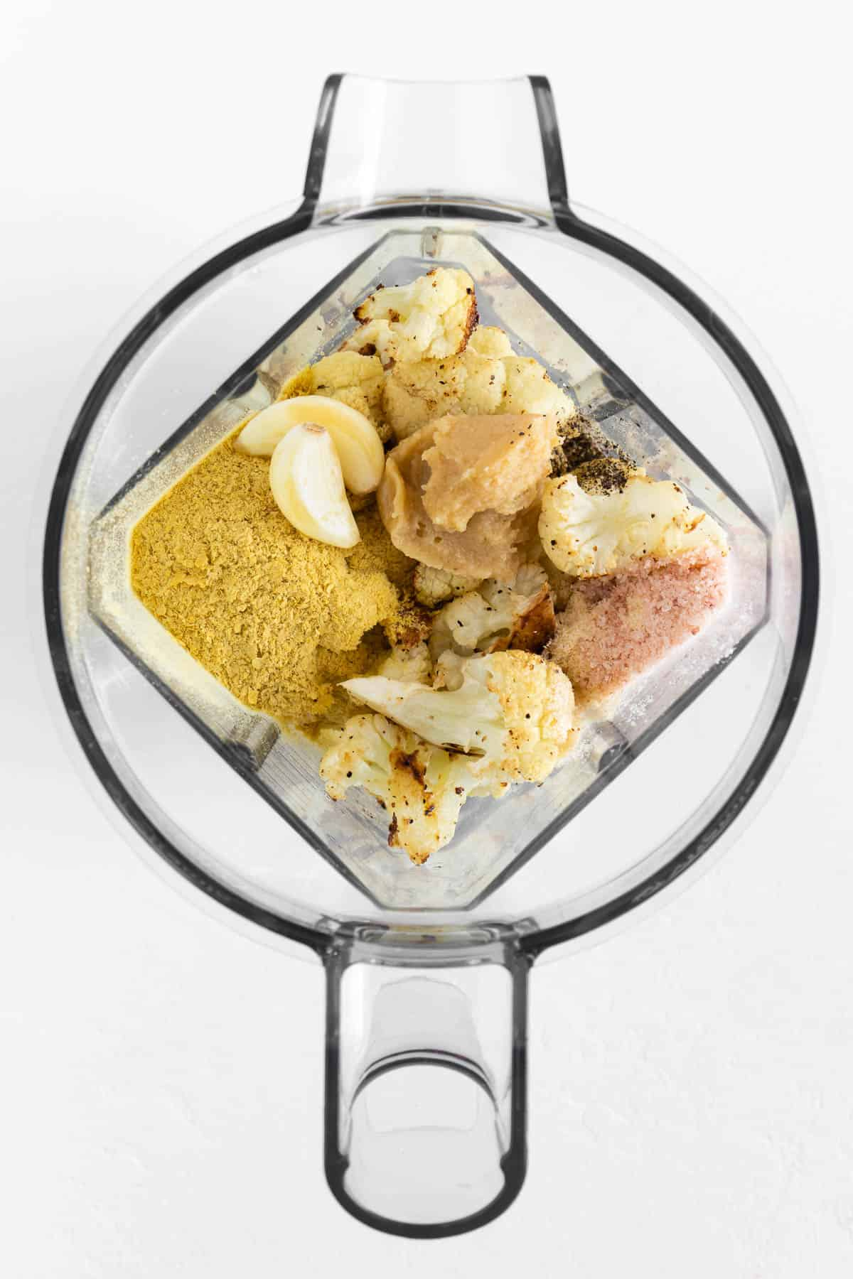 cauliflower, nutritional yeast, garlic cloves, salt, and mellow white miso paste inside a blender