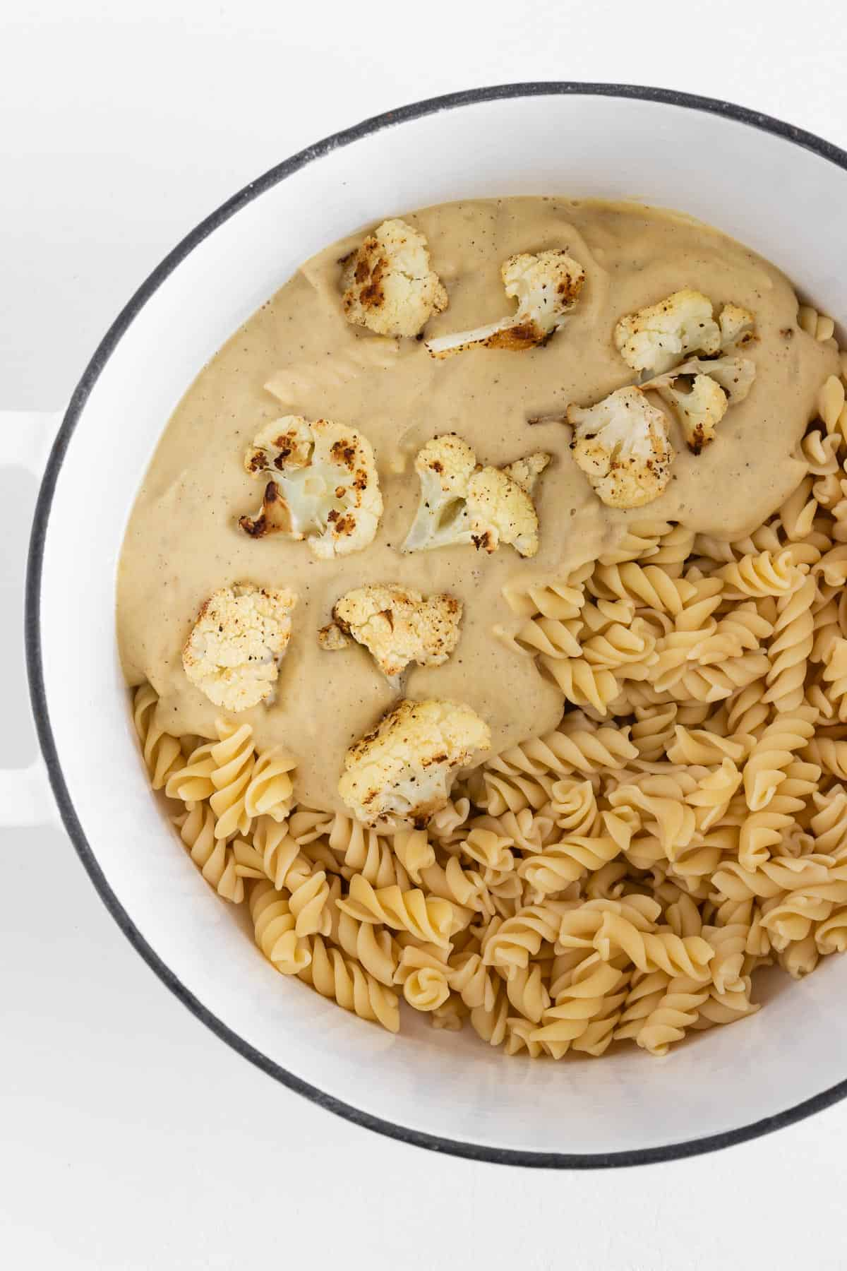 rotini pasta inside a white sauce pot with cauliflower alfredo sauce and roasted cauliflower florets