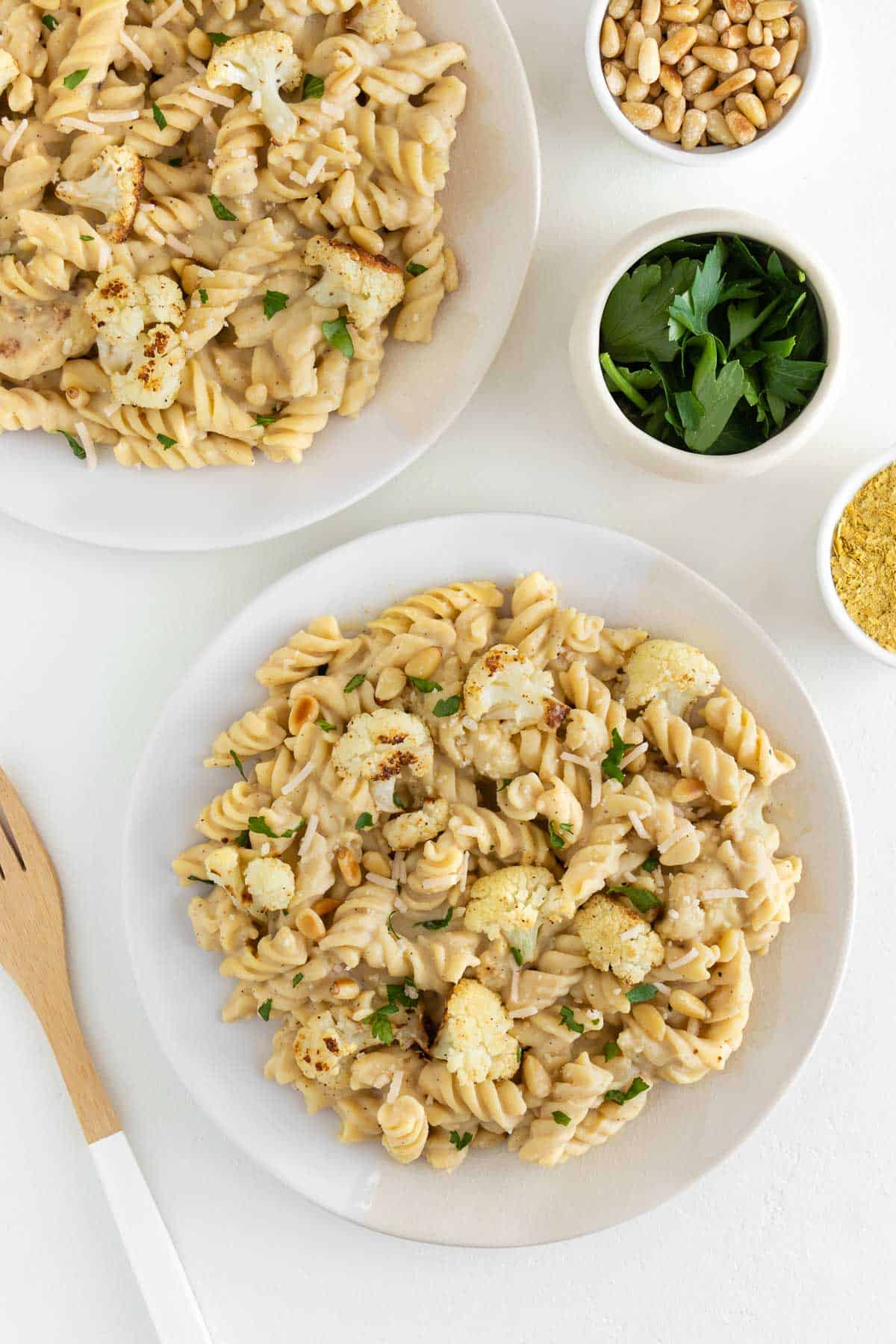two ceramic plates topped with roasted cauliflower alfredo, surrounded by a wooden fork and small bowls with parsley and pine nuts