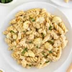 roasted cauliflower alfredo pasta on two ceramic plates beside a bowl of pine nuts and parsley