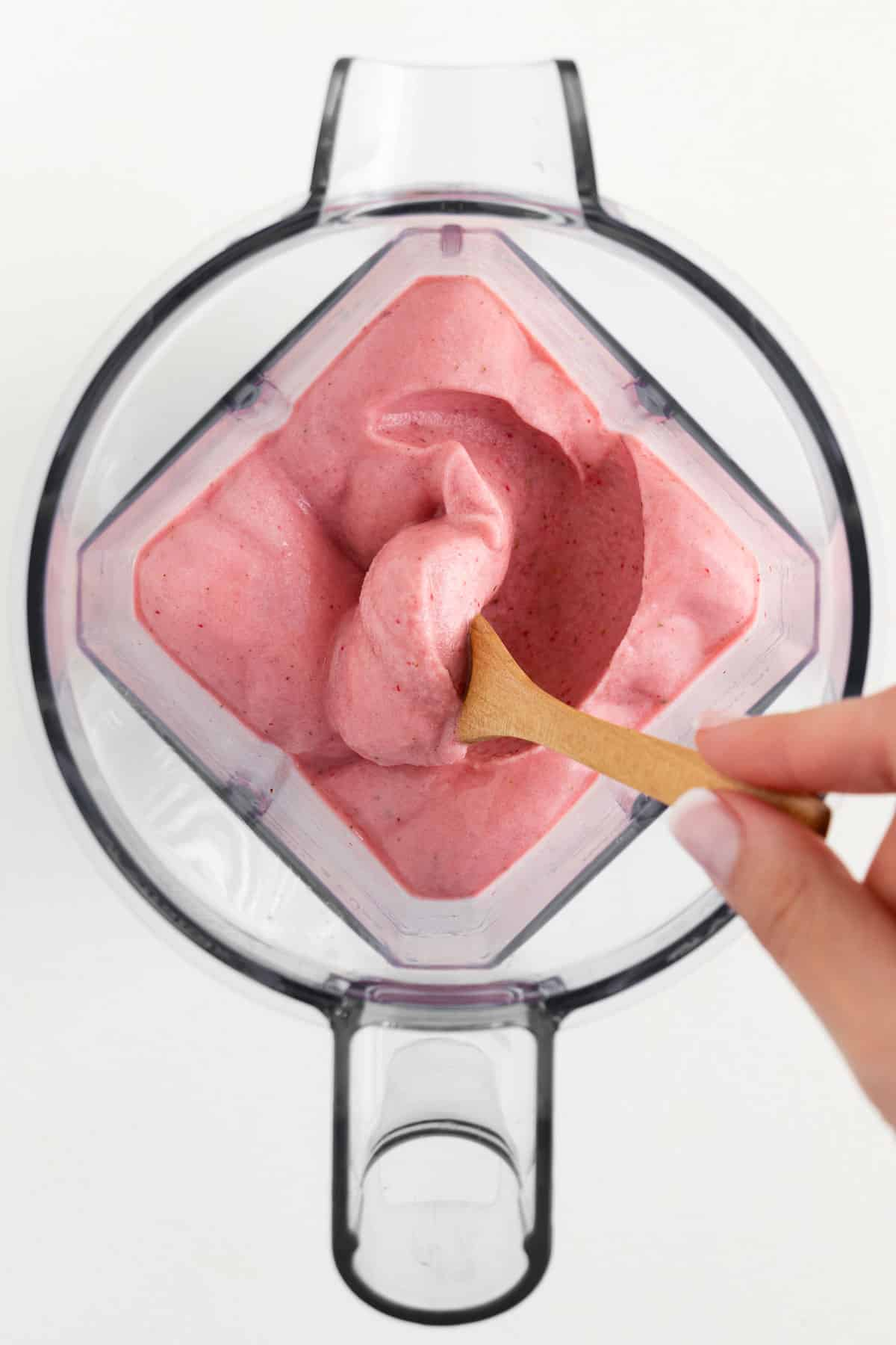 a hand holding a spoon scooping a thick pink smoothie inside a blender