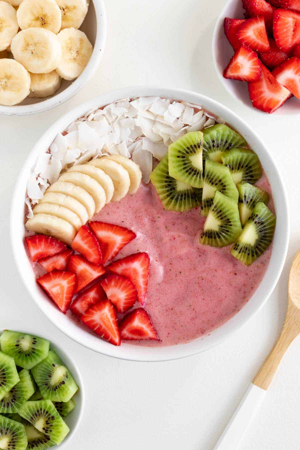 a strawberry kiwi smoothie bowl surrounded by bowls of sliced banana, strawberries, and kiwi fruit