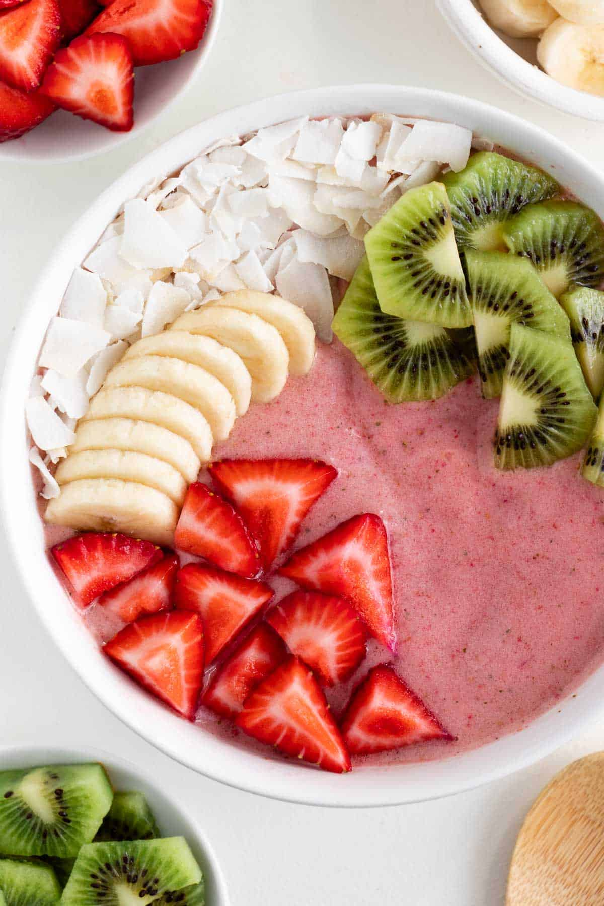 a strawberry smoothie bowl topped with coconut flakes, banana, kiwi fruit, and berries