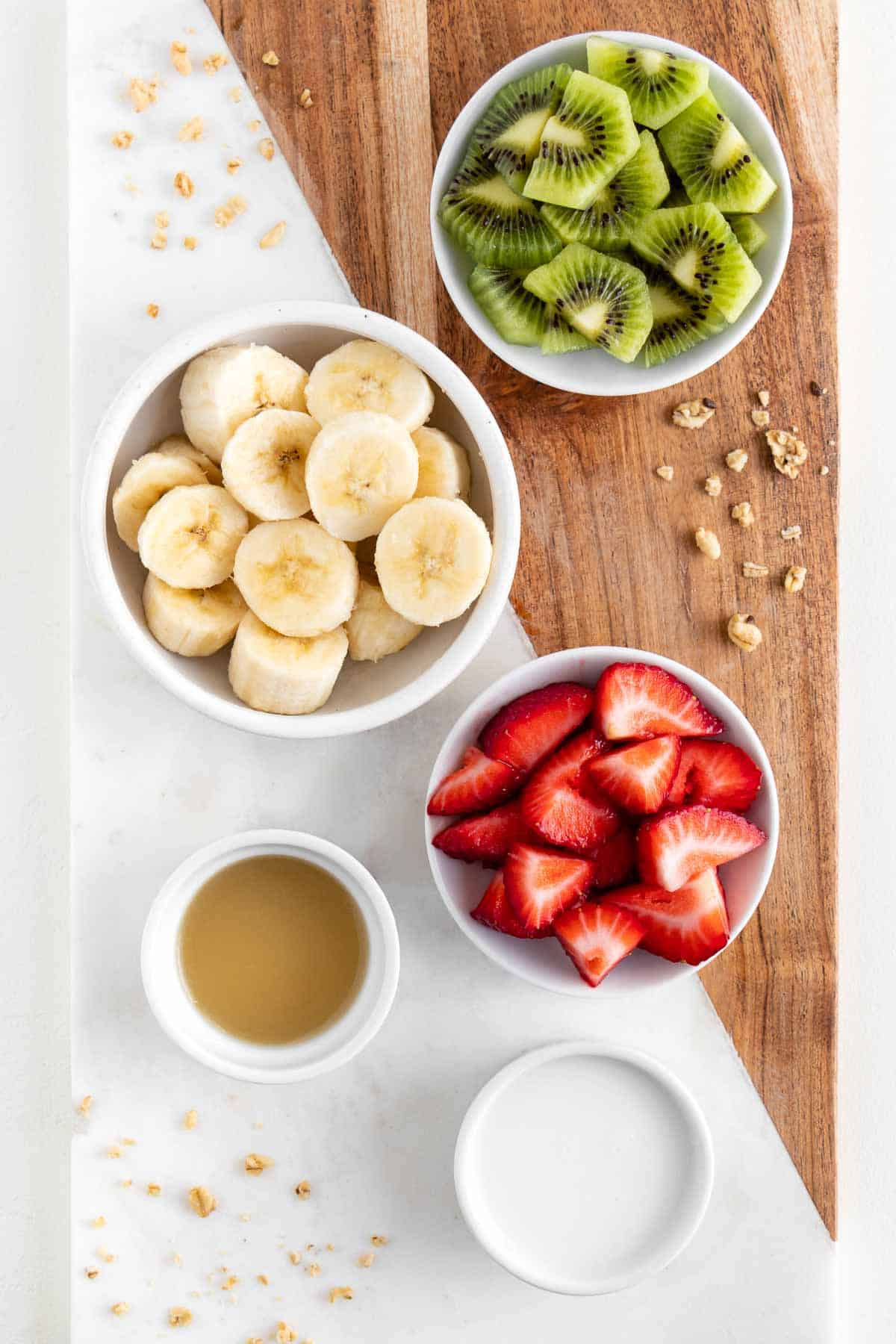 a marble and wood cutting board topped with bowls of banana, kiwi fruit, berries, lime juice, and almond milk