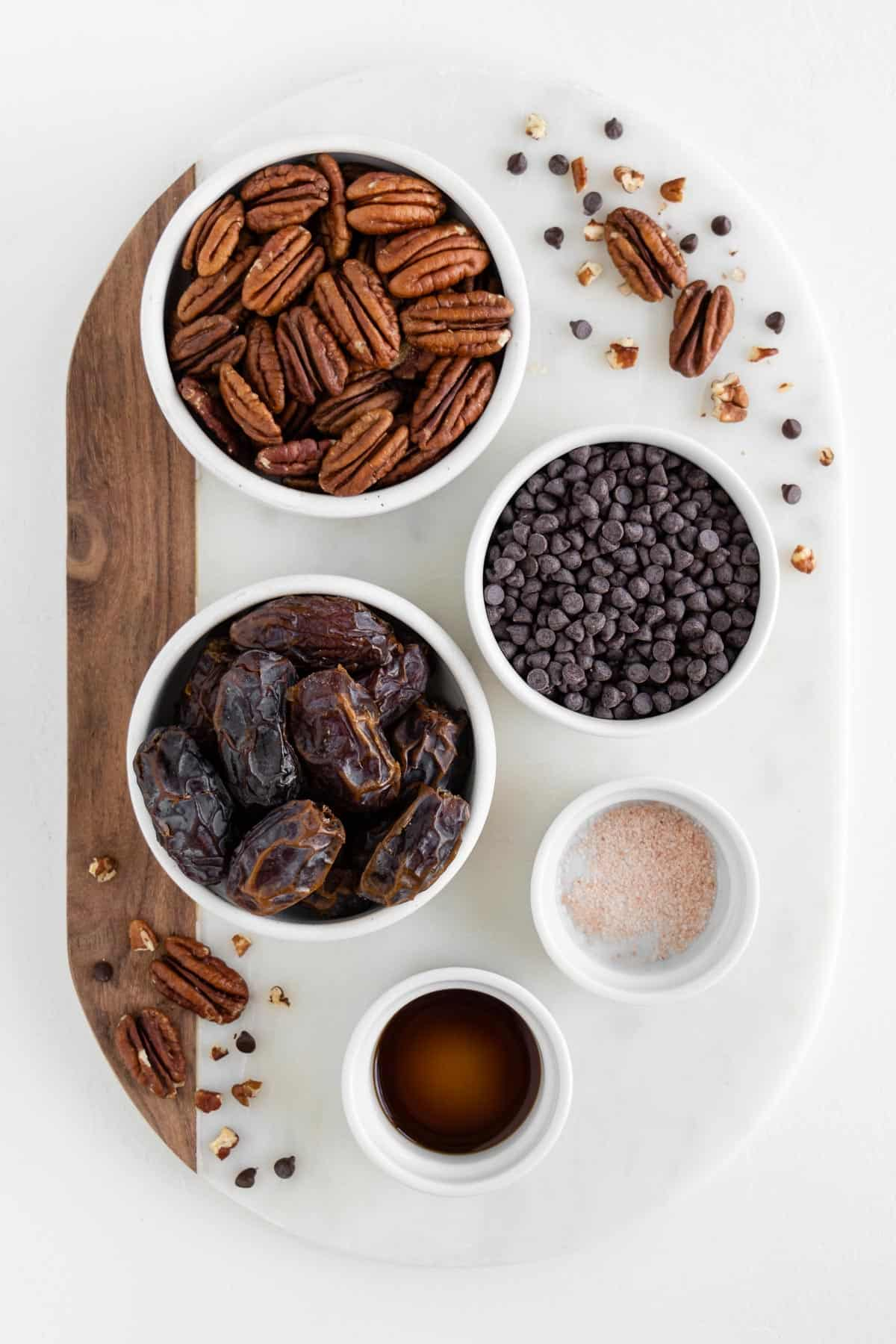a marble board with bowls of raw pecans, medjool dates, chocolate chips, salt, and vanilla extract